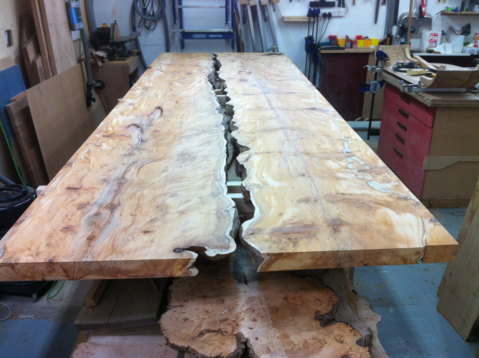 The positioned outer side of each piece of yew is made wider by adding along the waney edge with further yew, then cut straight for the table side edges and sanded before the first of three oilings.