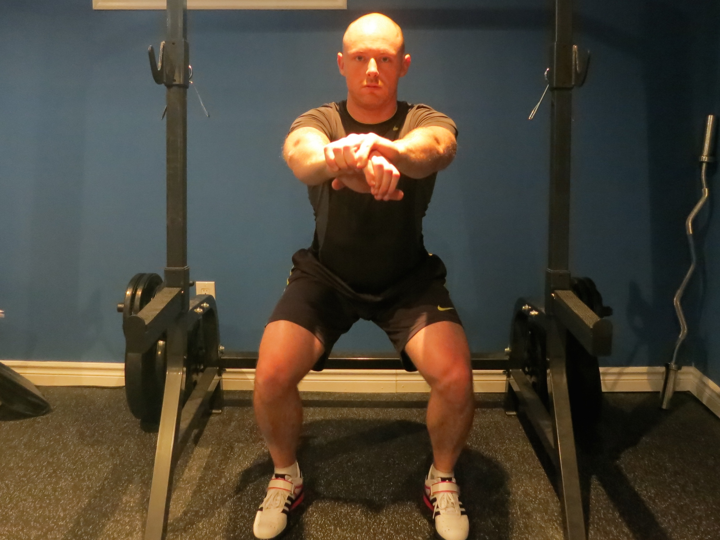 Knees bend and track towards middle toe. Consciously drive and maintain wide knees throughout the full range of motion. Weight is distributed through the heels and outside of the feet.