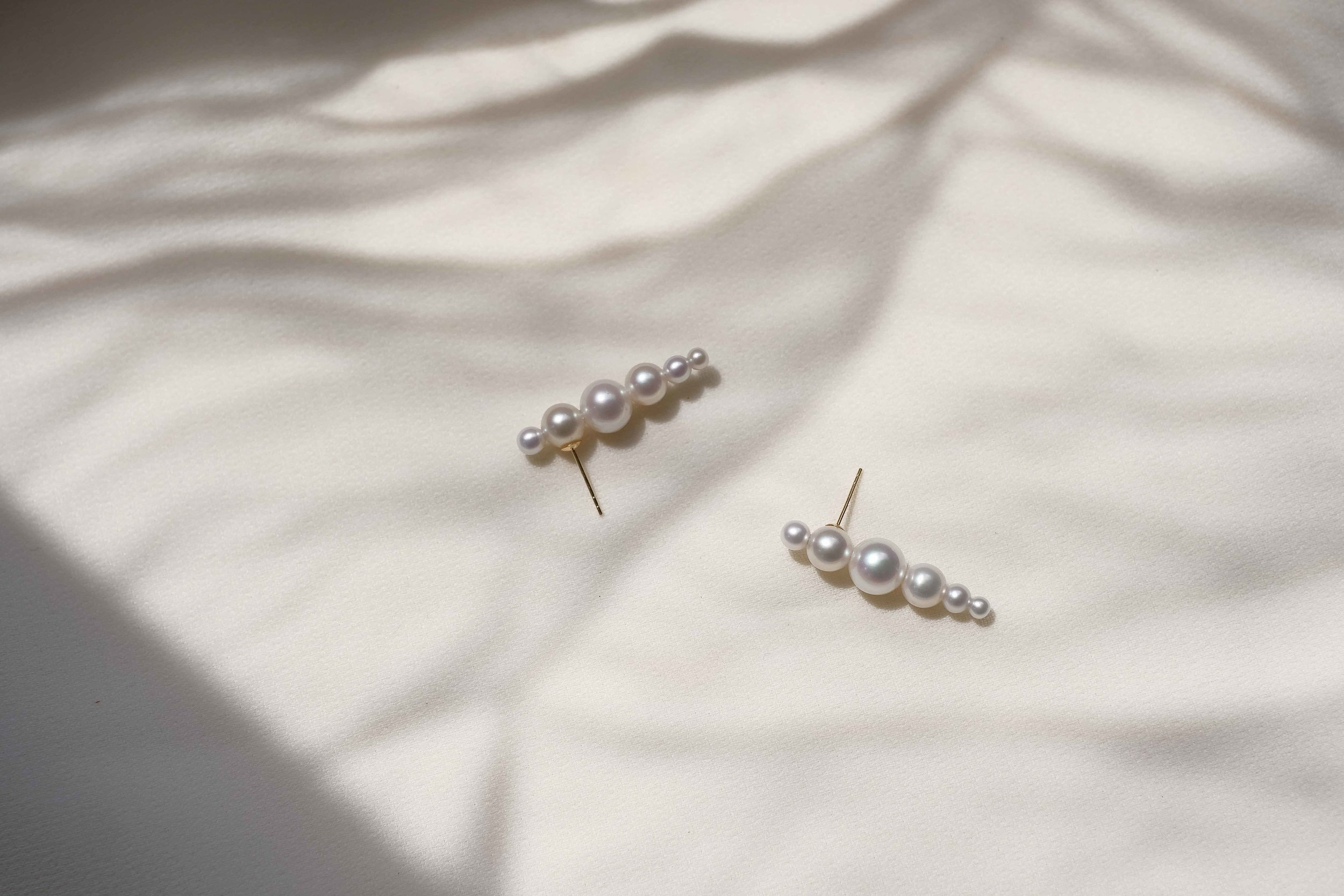Versed in 18k gold and fresh water pearls, the sequence of pearls arranged in a rhythmic sequence, extending in elegance.