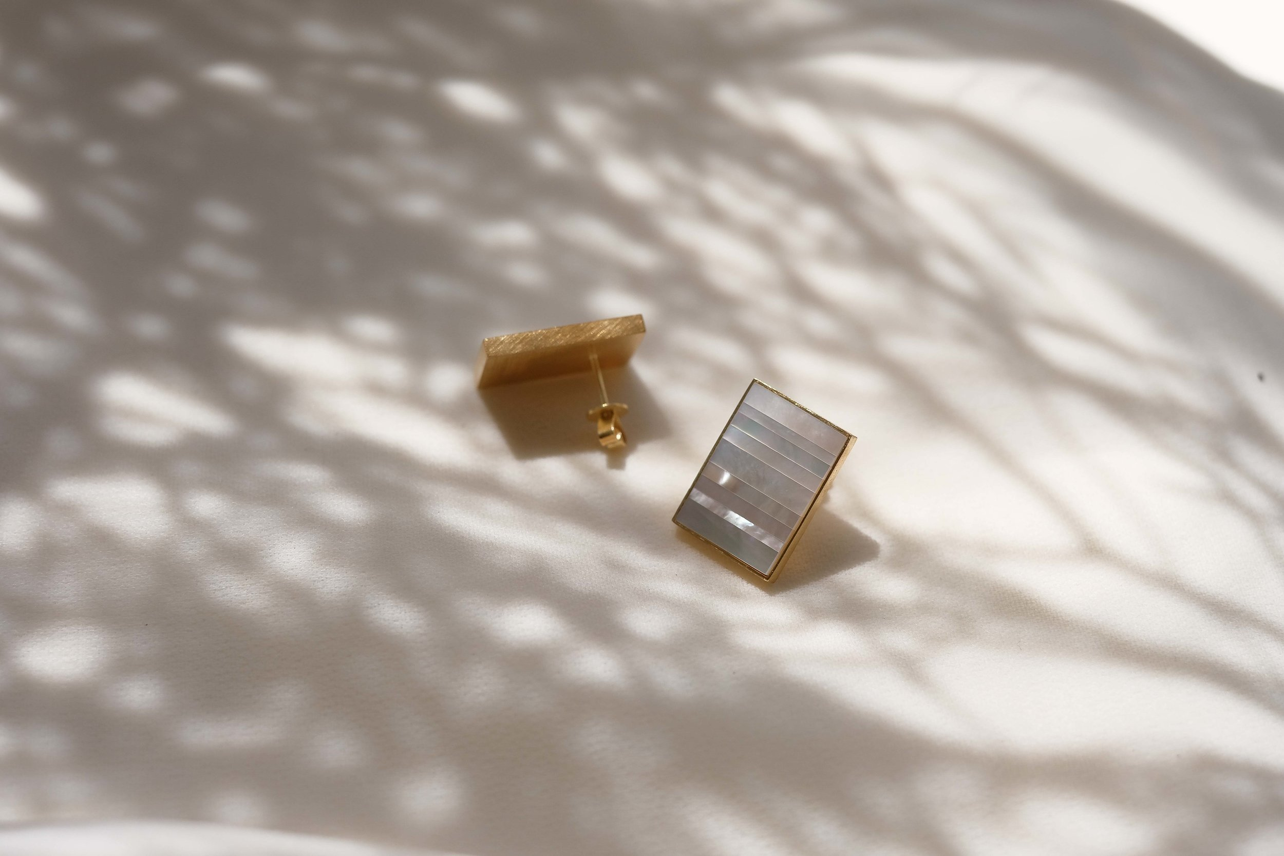 Medley Earrings (IIIII)   Mismatched strips of nacre are pieced together into this medley of dreamy treasure. Viewed from different angles, the gem gleams in a variety of soft pastel hues.
