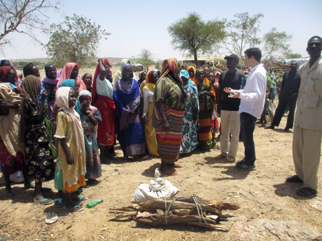 RI Advocate Michael Boyce speaking with refugees at a firewood distribution in Farchana. The bundled wood on the ground is what is given to three families in one month.