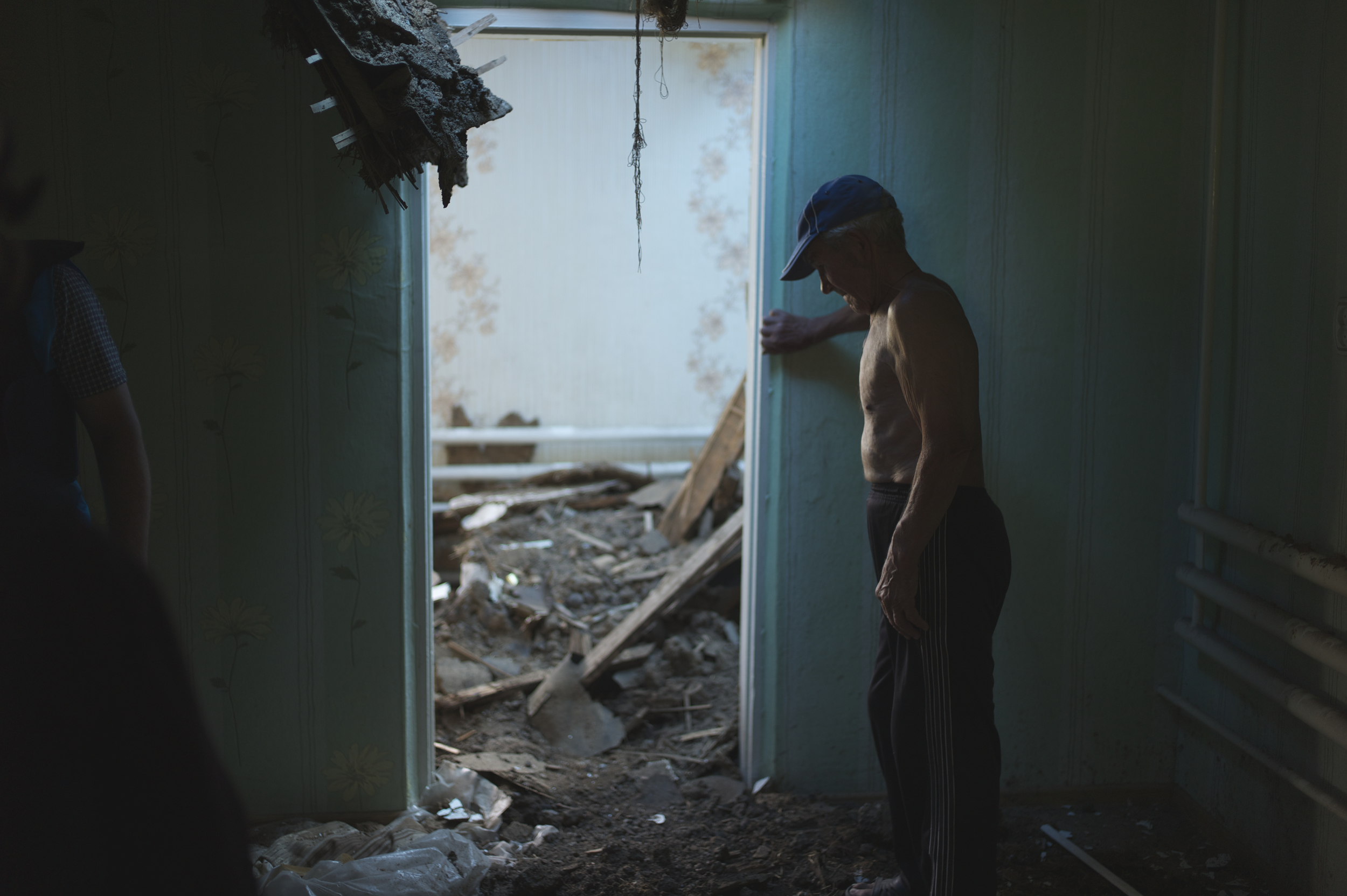 A man assesses the damage to his home by shelling from rebel forces in the NGCA. Most IDPs have found immediate housing with friends or relatives, but there are increasing needs for longer-term housing solutions for the displaced. Photo: Patrick Breslin