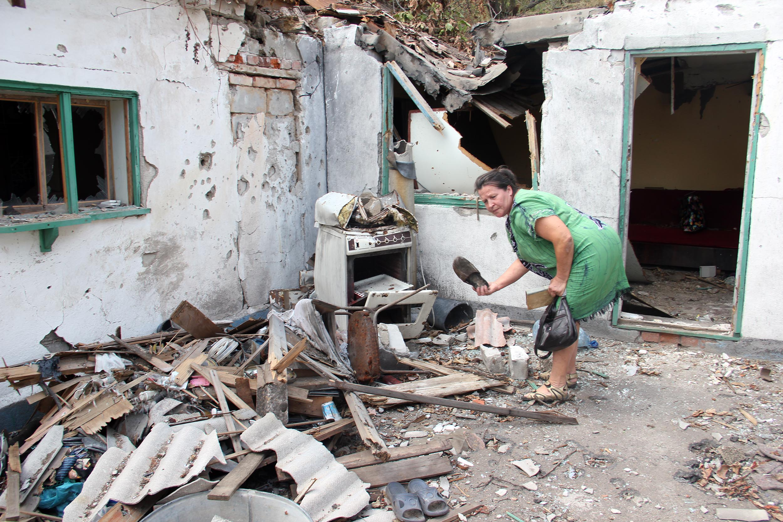 A displaced woman in Mariupol returned to her house on the line of contact to look at the damage done when it was shelled. She fled her home during the shelling, and came back to retrieve some possessions. Photo: UNHCR