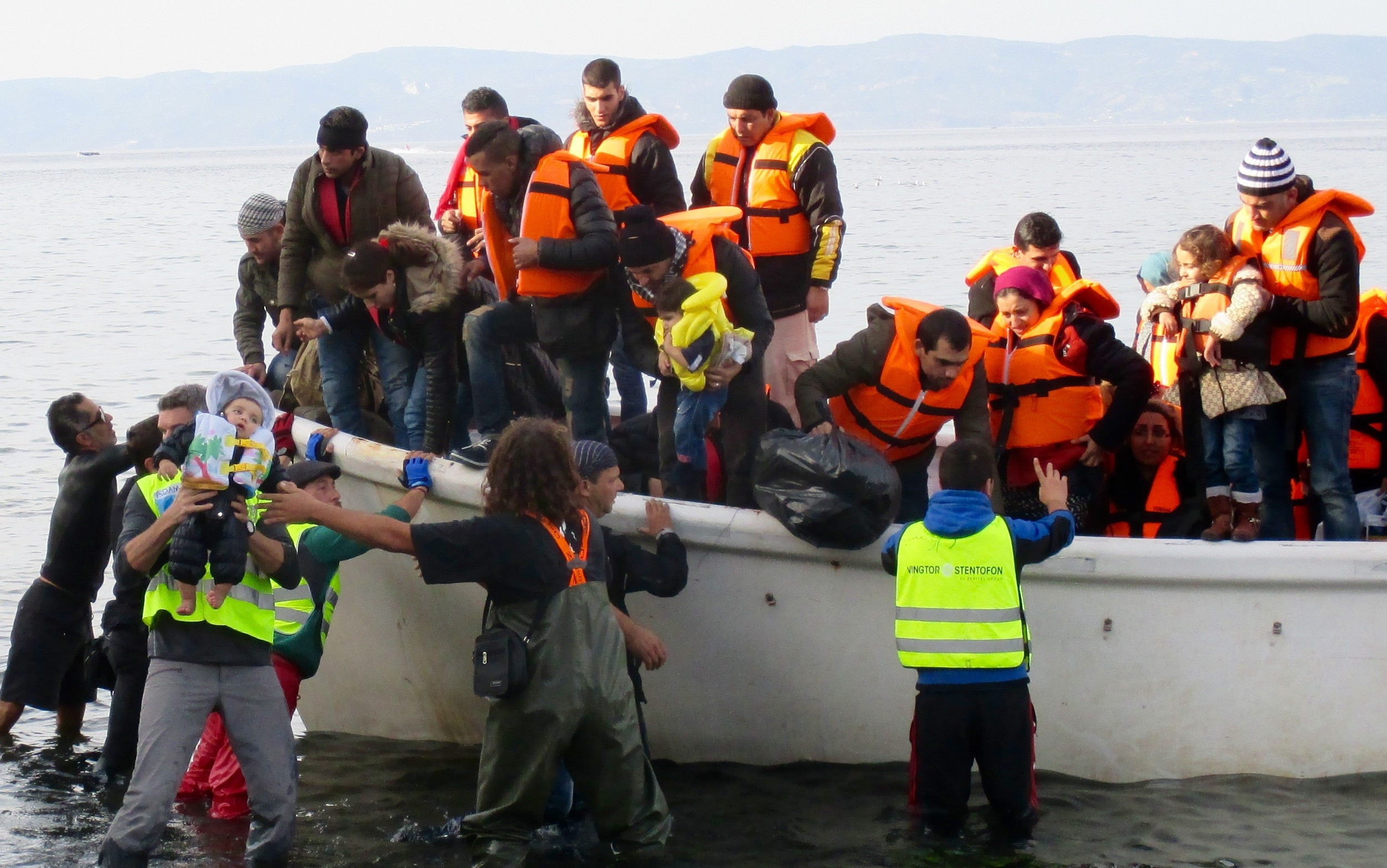 Arriving in a coastguard boat that rescued them from their sinking dinghy, children are offloaded first by a variety of different volunteers organizations acting as first responders on the shore.
