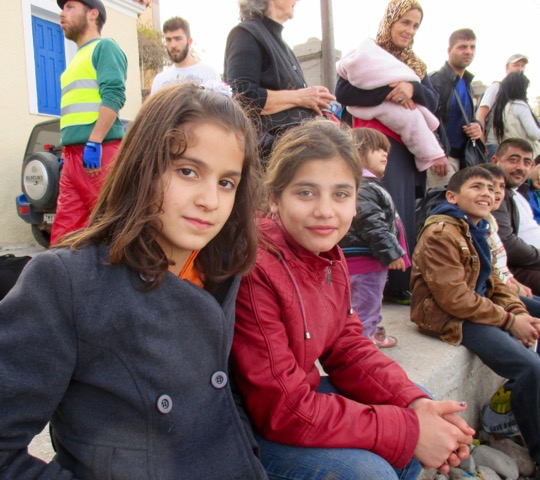 Two young Syrian girls rest before walking to the transit center in Lesvos.