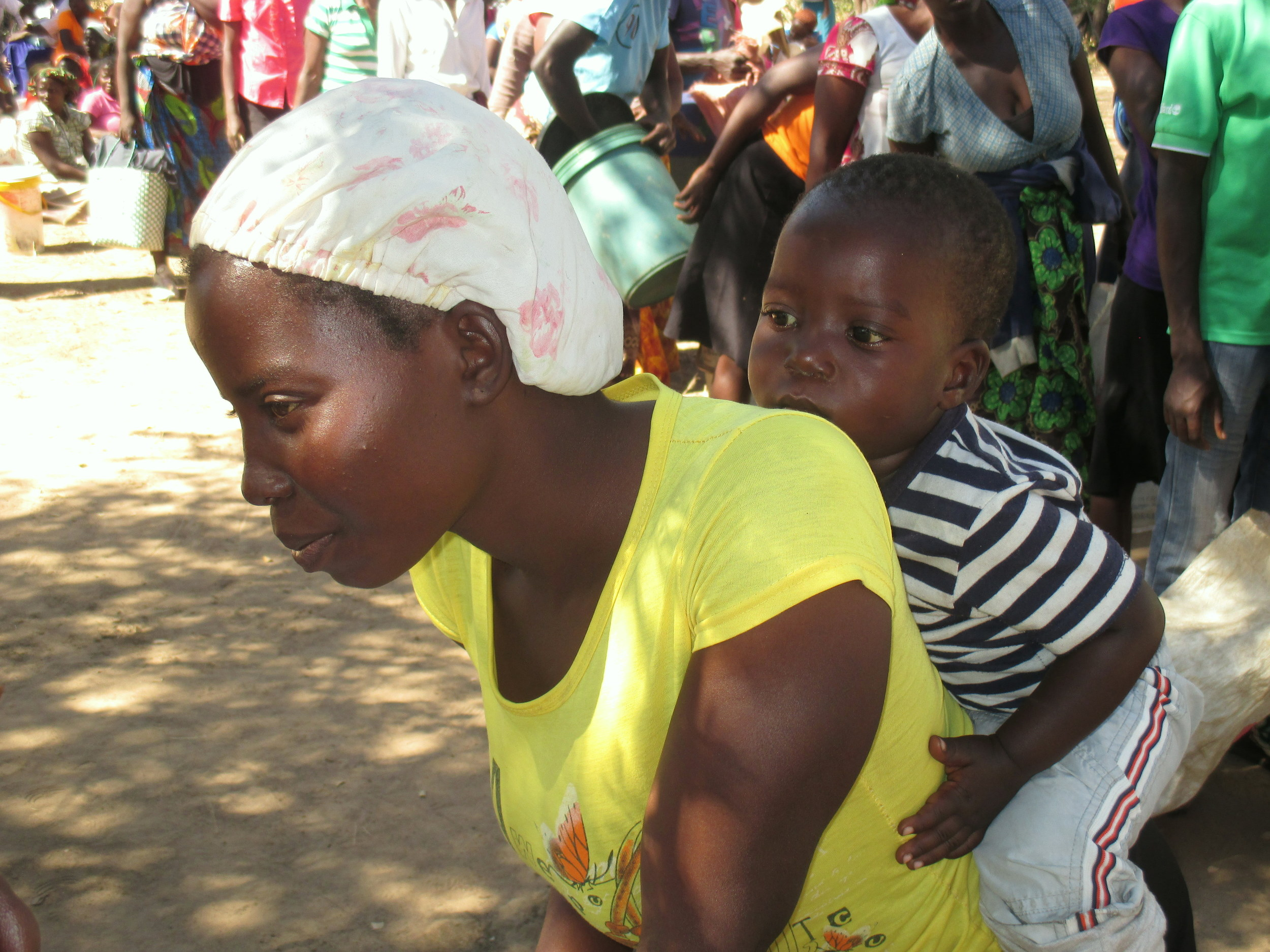 A mother waits in line at a UN World Food Program food distribution site in Binga District. This was the last day of the monthly food distributions, leaving many parents wondering where their children's next meal will come from.