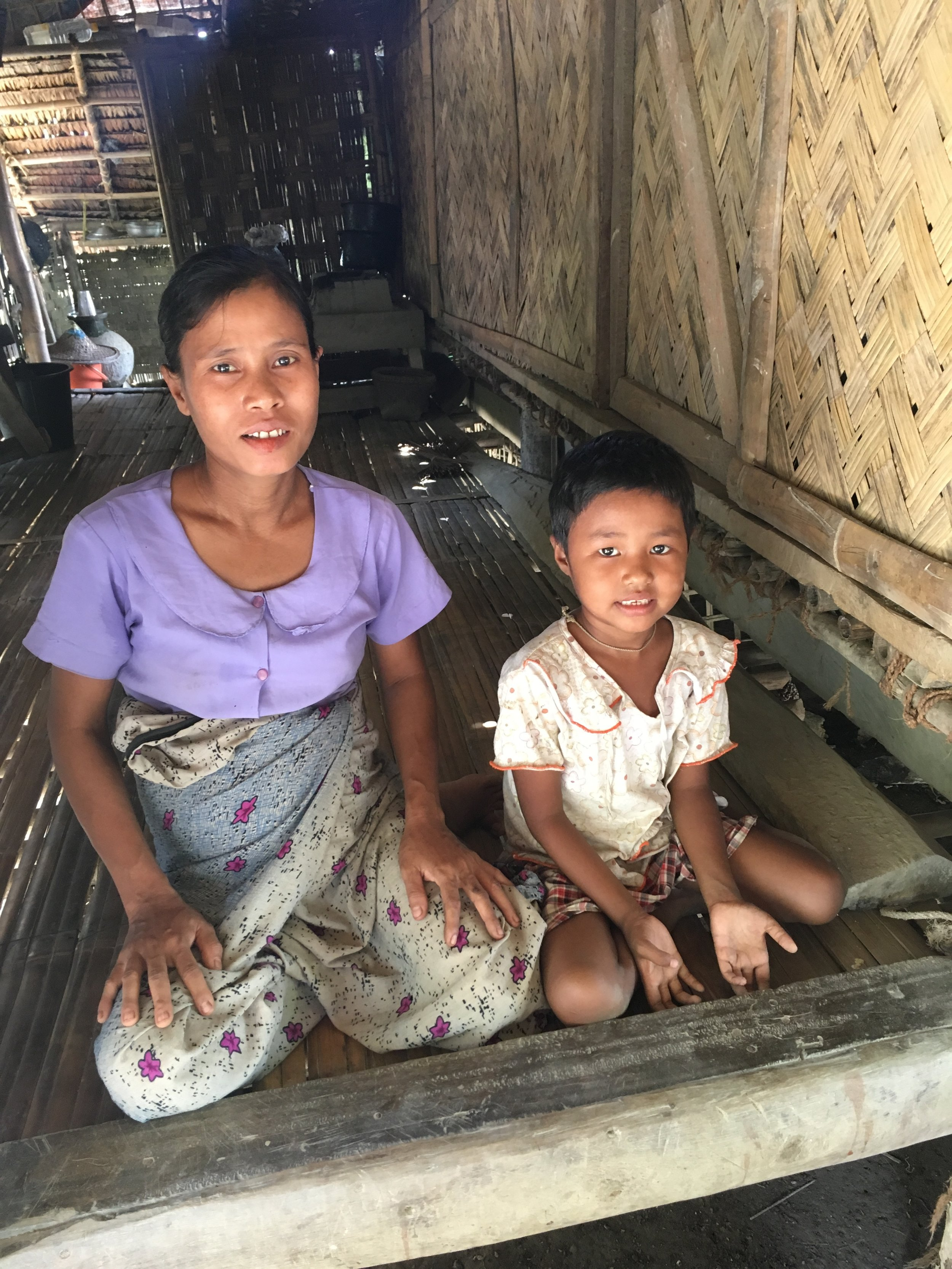 """We are casual workers, and after the floods, there is less work for us."" In a remote village in the Mimbya Township of Rakhine State, the 2015 floods swept away Zaw's* family's small bamboo house, their few belongings, and all of their animals (six chickens and a pig). Since the 2015 floods damaged nearby paddy fields, Zaw and her husband, both casual workers, now face increased competition for whatever work opportunities are available, and their daily wages are half of what they were before the floods. Five months pregnant and the mother of two, Zaw sits with her youngest daughter (pictured) in their reconstructed basic bamboo shelter and explains that, due to the family's now much-reduced weekly income, Zaw is no longer able to afford the fee to send her youngest child, Yu* (pictured), to school."