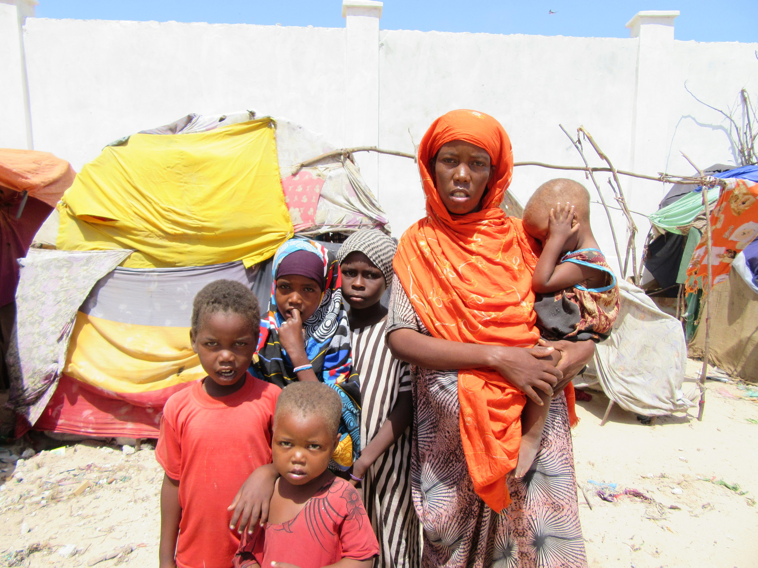 """Eight months pregnant, this young mother arrived in Mogadishu four days ago with her husband and four of her children having walked for 20 days to get here. """"First we had drought and our animals died. Then fighting broke out in the village forcing us to flee in all directions. I lost three of my children in the fighting."""" She and her family are now living in this camp for internally displaced persons (IDPs) where they don't yet even have any shelter to sleep under."""