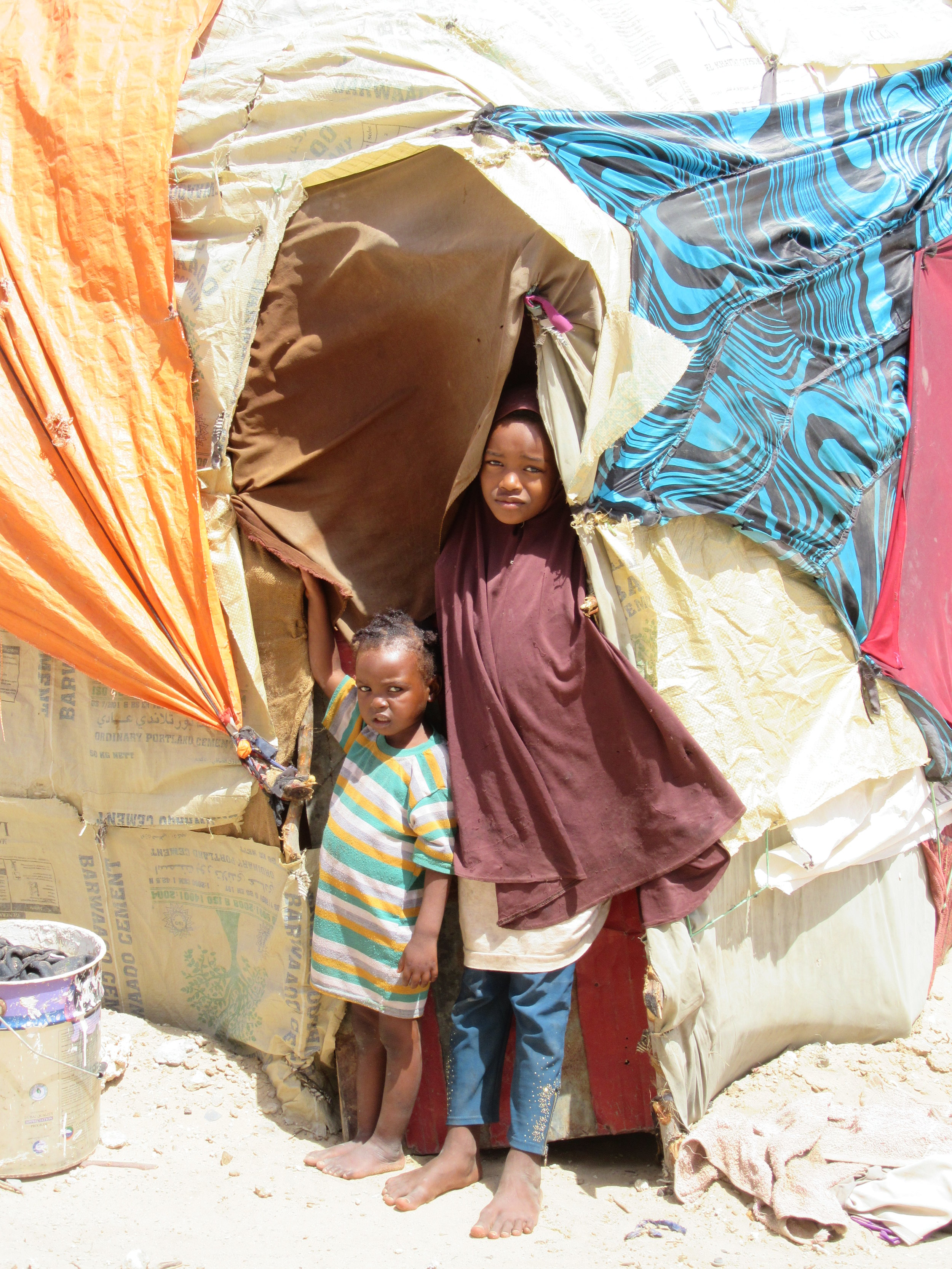 New arrivals construct makeshift shelters using tarps, sticks, and cloth.