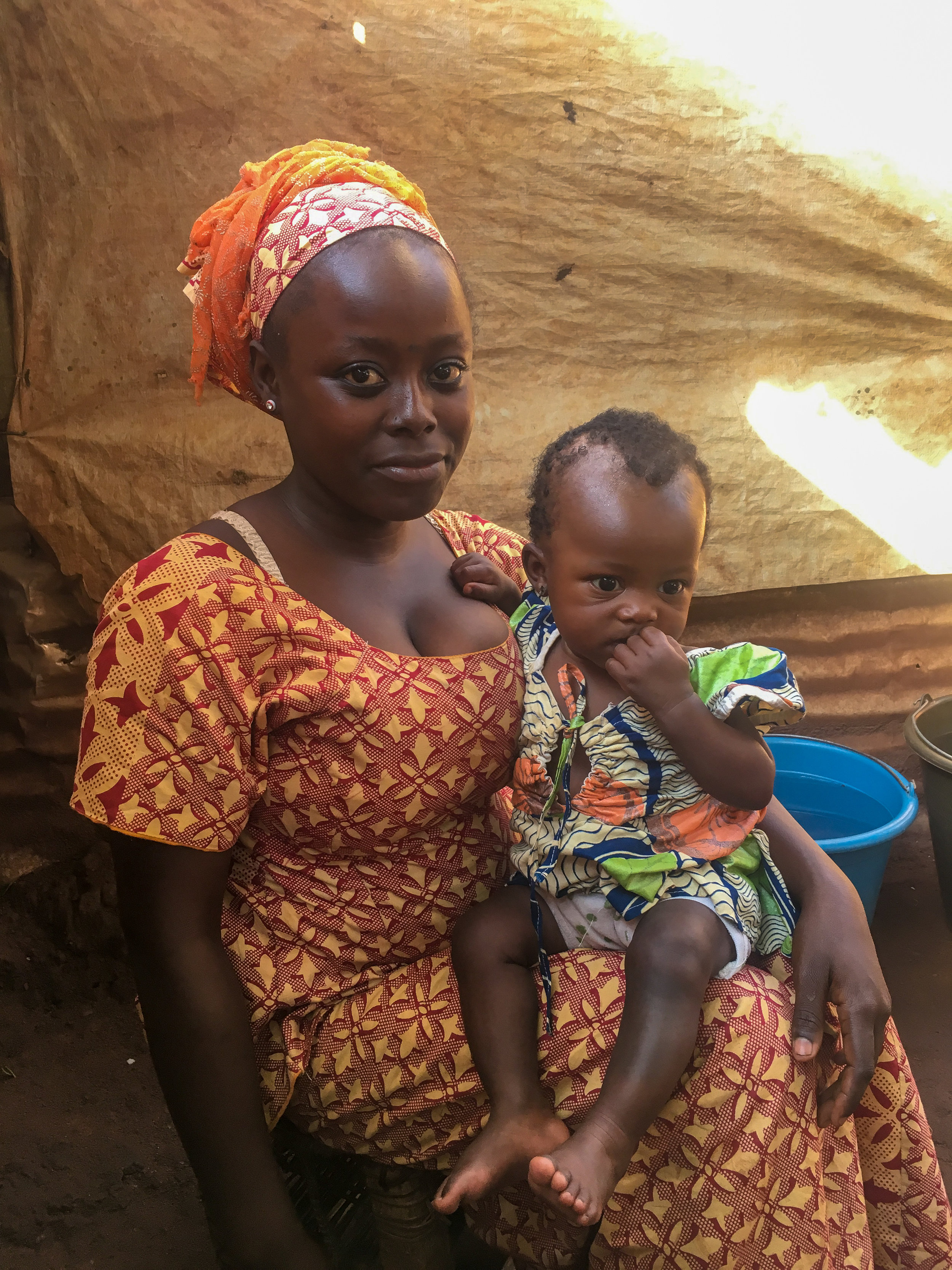 A young woman holds her child in the Bangassou IDP camp where she gave birth. Photo by Refugees International.