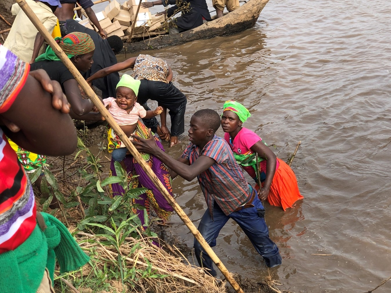 People displaced by Cyclone Idai outside of Chimoio desperately cross a river to receive their first food distribution following the storm. More than two months after the cyclone, some Mozambicans who lost their homes and farmland were still searching for ways to feed themselves and their families.