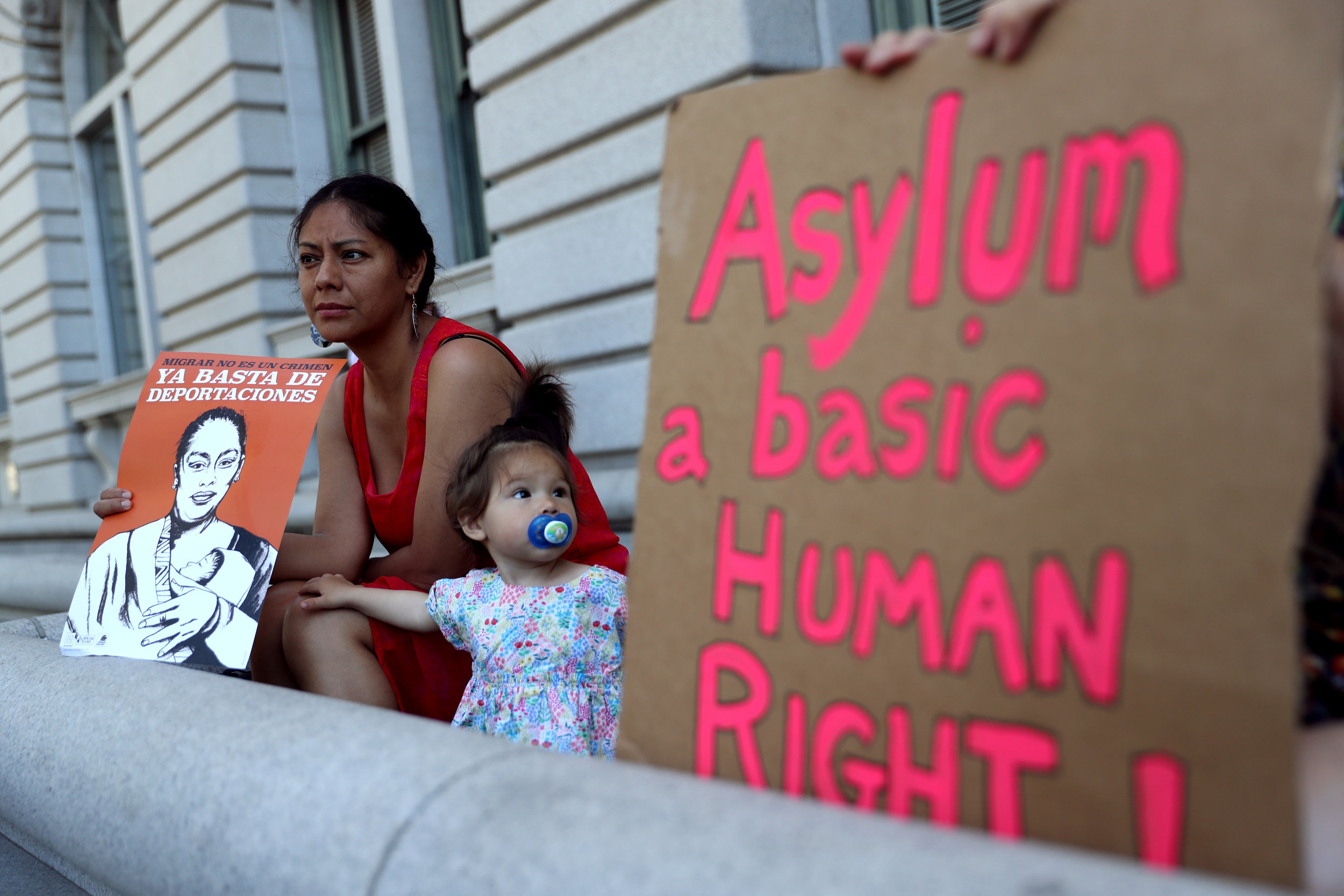 A protester holds a sign during a demonstration outside of the James R. Browning U.S. Courthouse in support of restoring protections for asylum seekers. Photo Credit: Justin Sullivan/Getty Images.