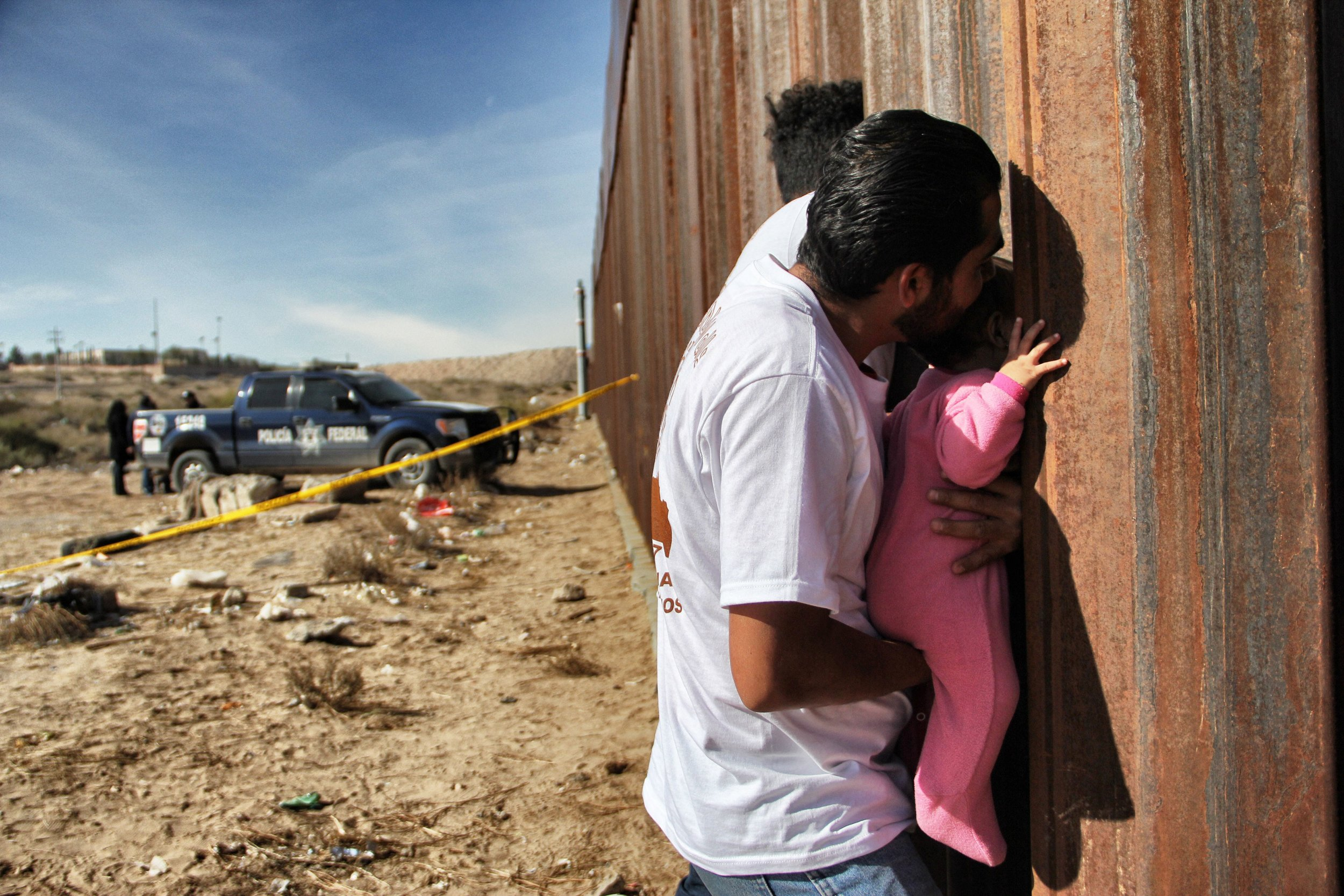 A man holds a baby up to the border wall between Mexico and United States. Photo Credit: HERIKA MARTINEZ/AFP/Getty Images.