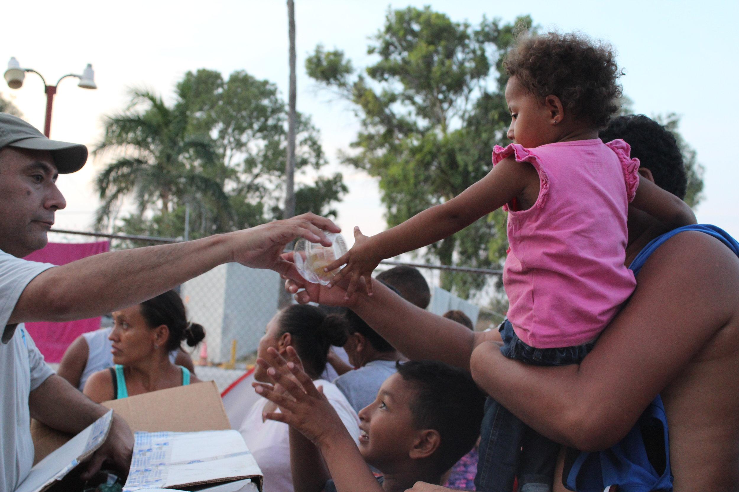 American volunteers provide food to returned asylum seekers.