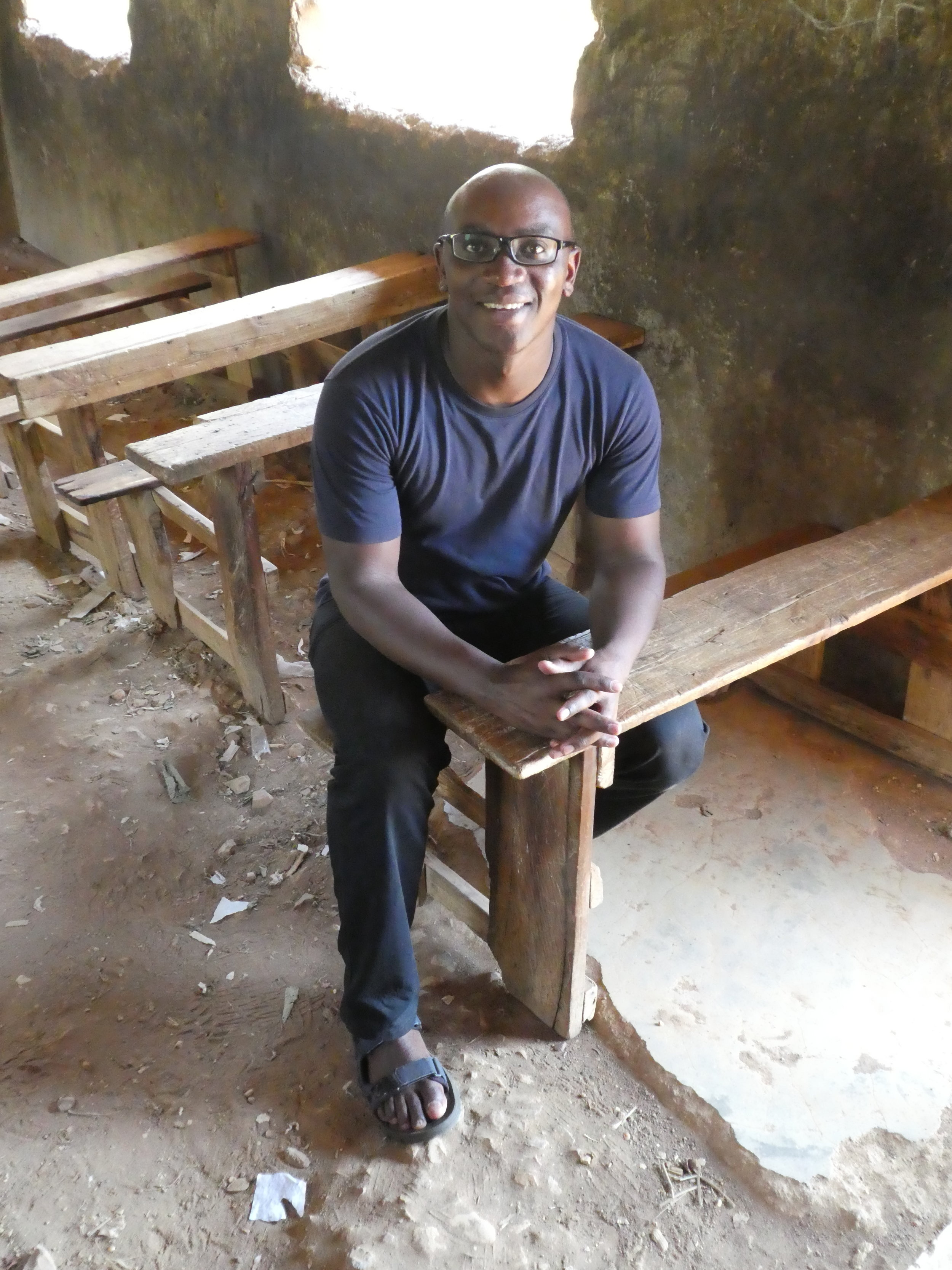 Dr. Erick Komolo revisiting the desk of his primary school classroom.