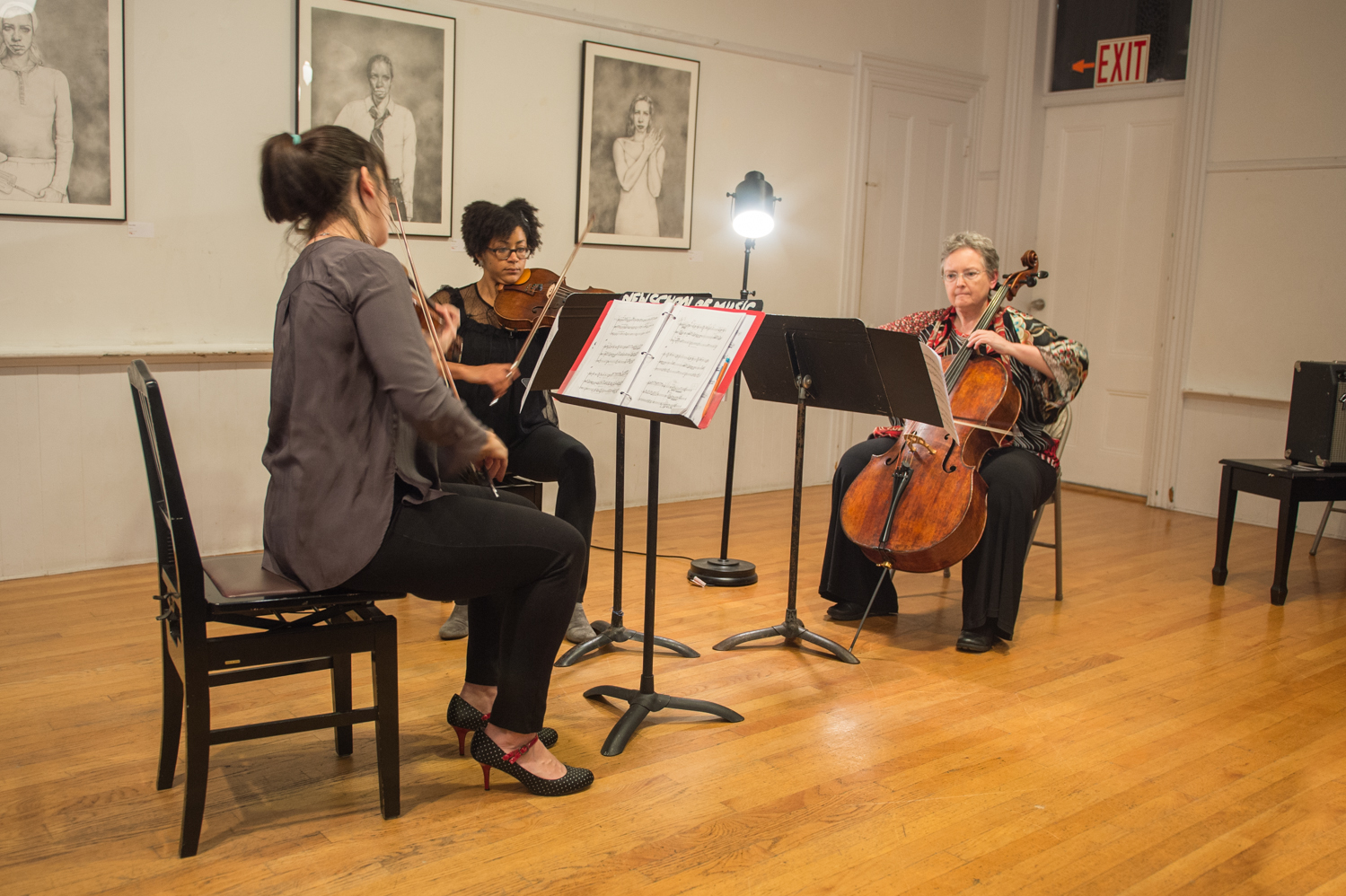 """Left to right: Gabriela Diaz, Ashleigh Gordon and Rhonda Rider performing Tania León's """"A Tres Voces."""" Taryn Wells's graphite drawings hang in the background. New Gallery Concert Series, with Castle of our Skins, Saturday evening at the New School of Music in Cambridge. Photograph Monika Bach Schroeder."""