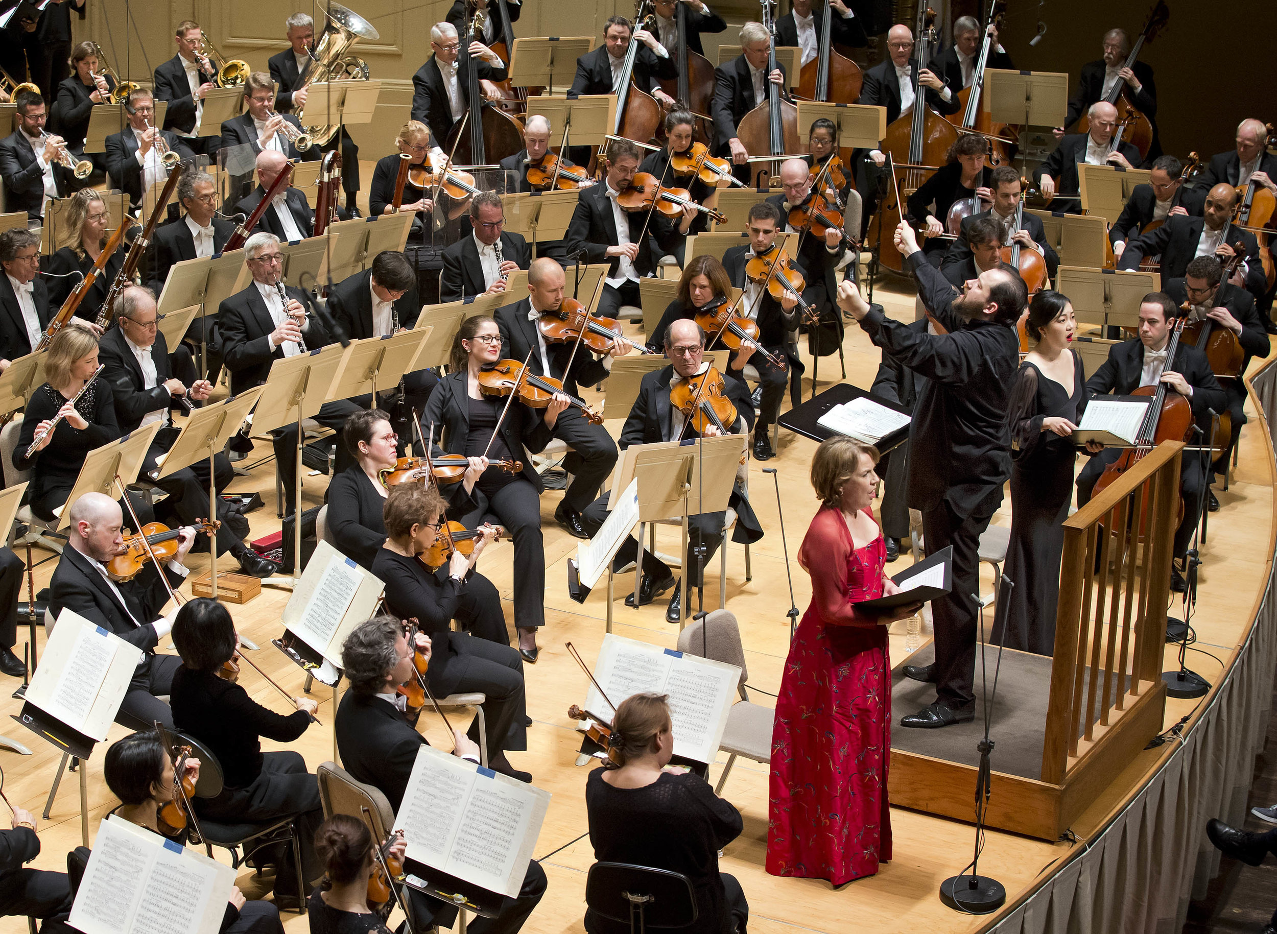 Andris Nelsons leads the Boston Symphony Orchestra and the Tanglewood Festival Chorus, with soloists Bernarda Fink (in red) and Ying Fang (in black, behind Nelsons), on Thursday, Oct. 25, 2018 in Symphony Hall. Winslow Townson photograph