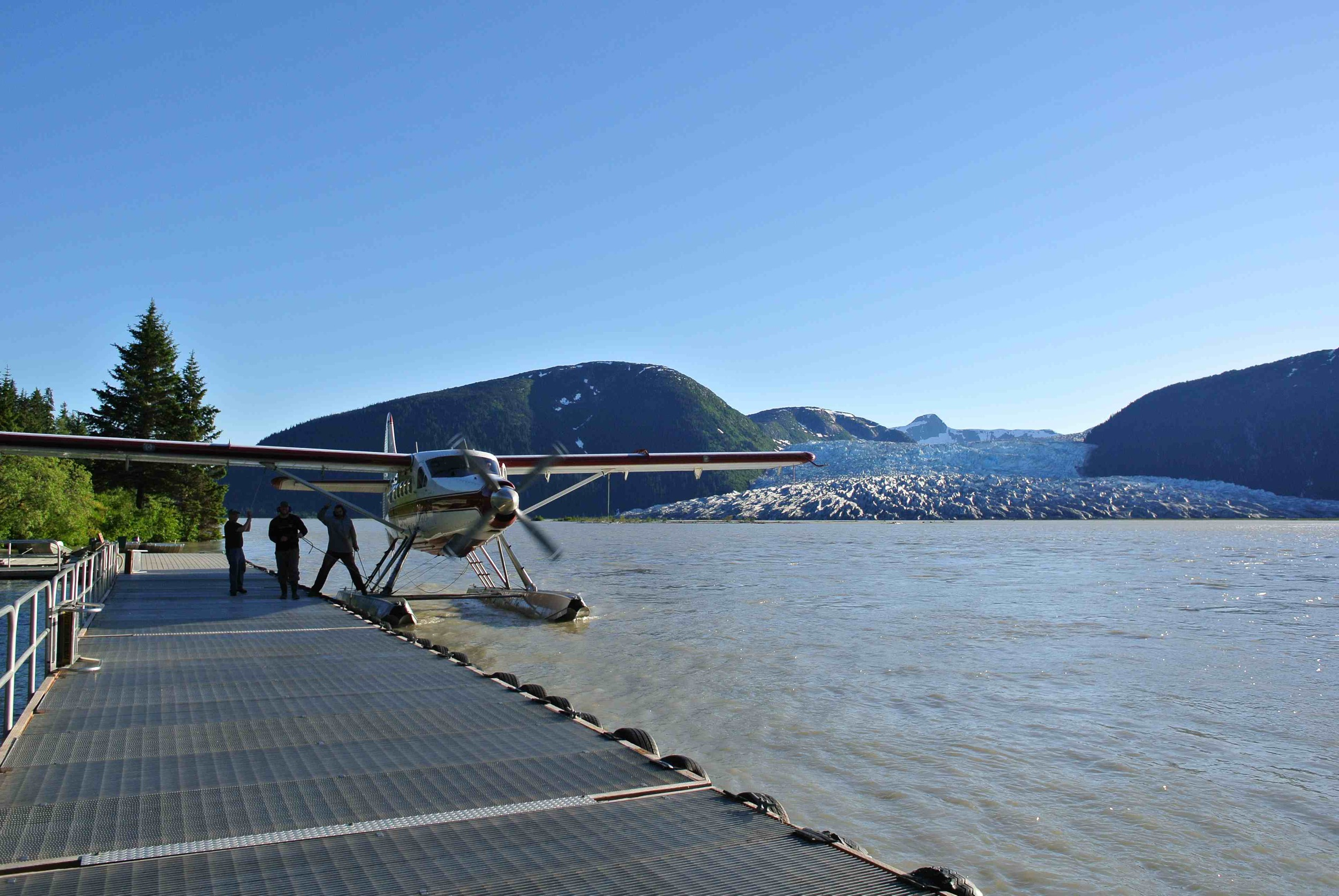 Airplane docking at Taku Lodge with Hole-in-the-Wall Glacier in the background. Photo: Salvatore G. Candela