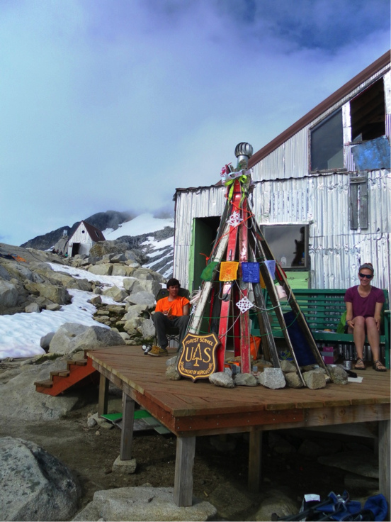 Alexei Doncov, and Leah Nelson enjoying the afternoon sun on the Camp 10 deck with our JIRPmas ski tree. Photo by Muriel Will.
