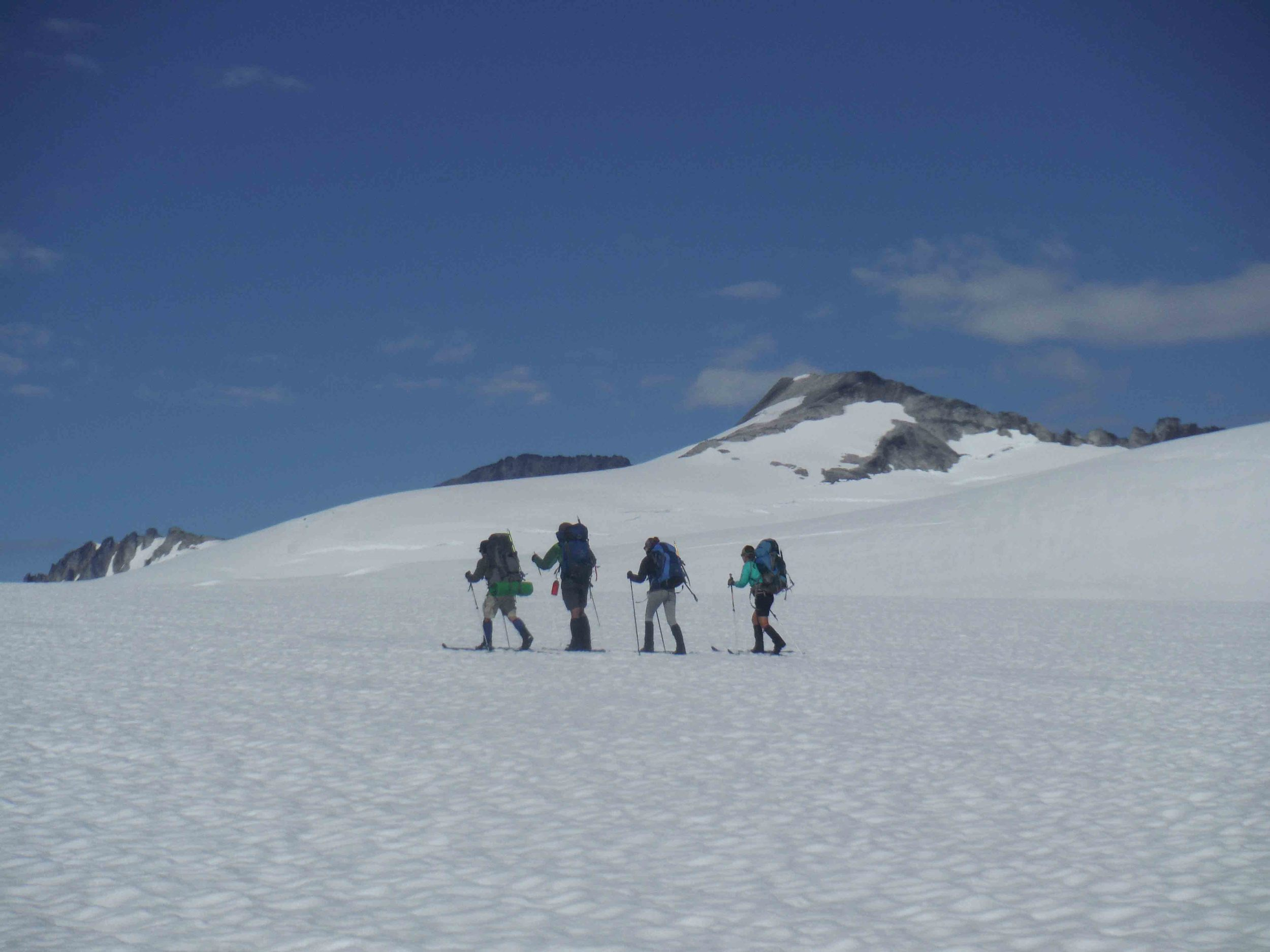 A group of four carries on in good spirits on Matthes Glacier. Mt. Moore - with Camp 8 on the ridge of rock pointing down towards the first skier - is in the background.  Photo by Sarah Bouckoms