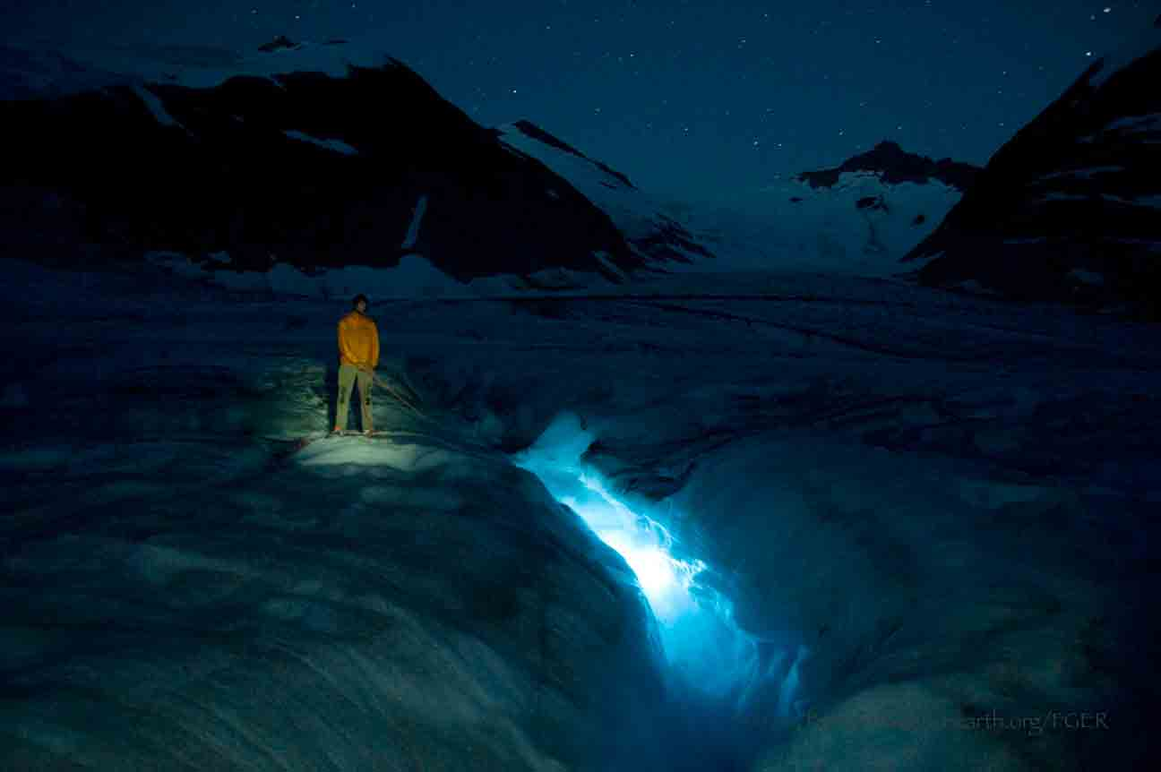 A crevasse is lit by headlamps in a night photo on Gilkey Glacier.  Photo by Jeffrey Barbee.