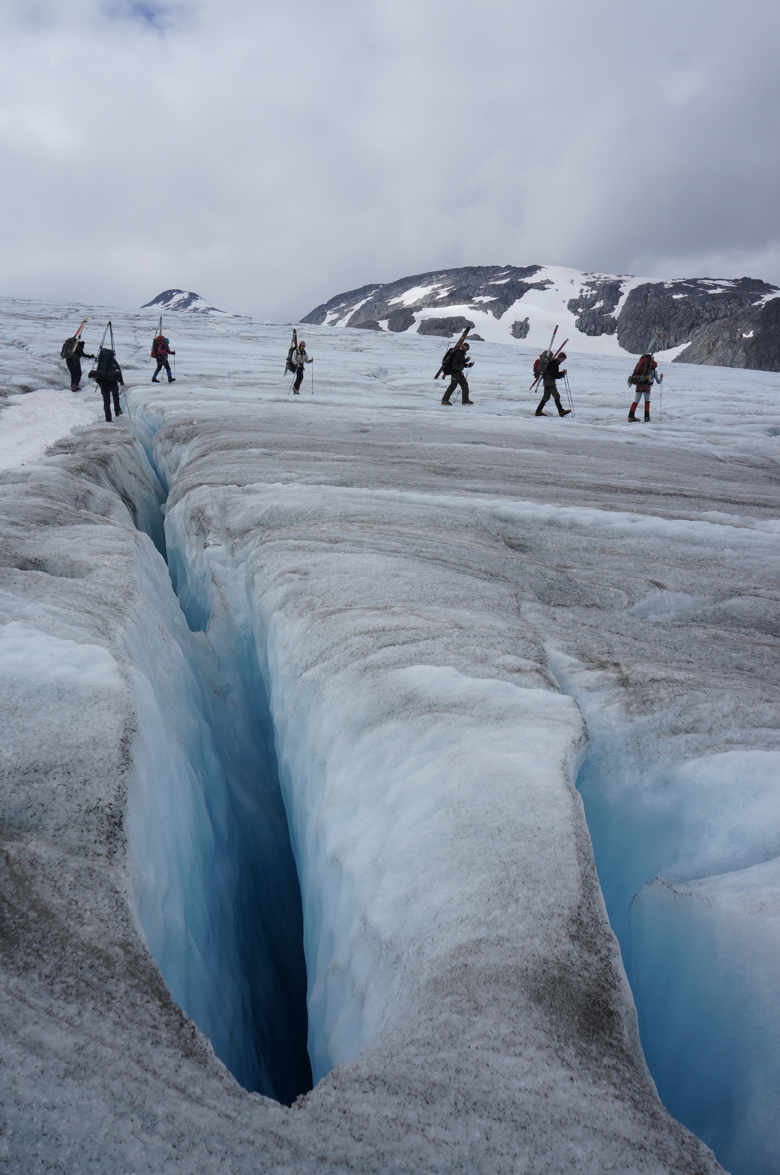 Members of trail party two navigate exposed blue ice and crevasses on the lower Lemon Creek glacier.  This was an added challenge for the final two trail parties, after days of rain increased ablation.  photo by Alexandre Mischler