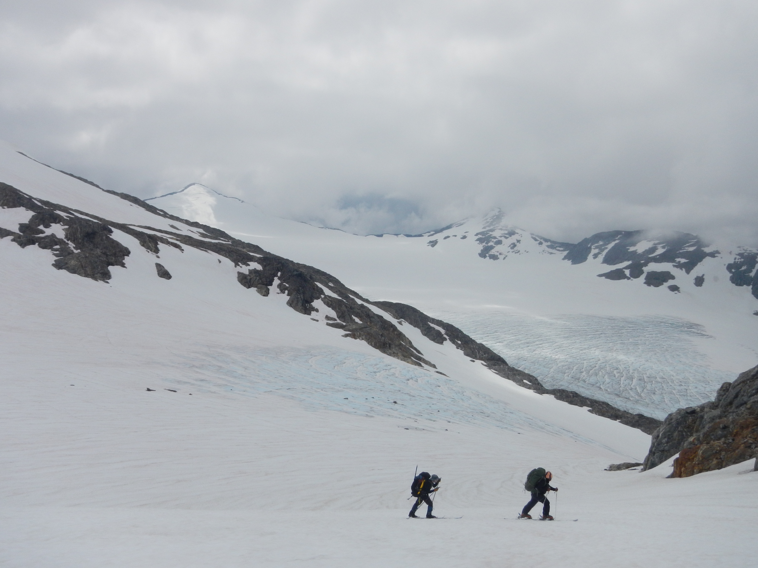 Staff member Stanley Pinchak and student Maya Smith ski up a track near the Thomas glacier with blue ice exposed on the Lemon Creek glacier in the lower background. photo by Natalie Raia