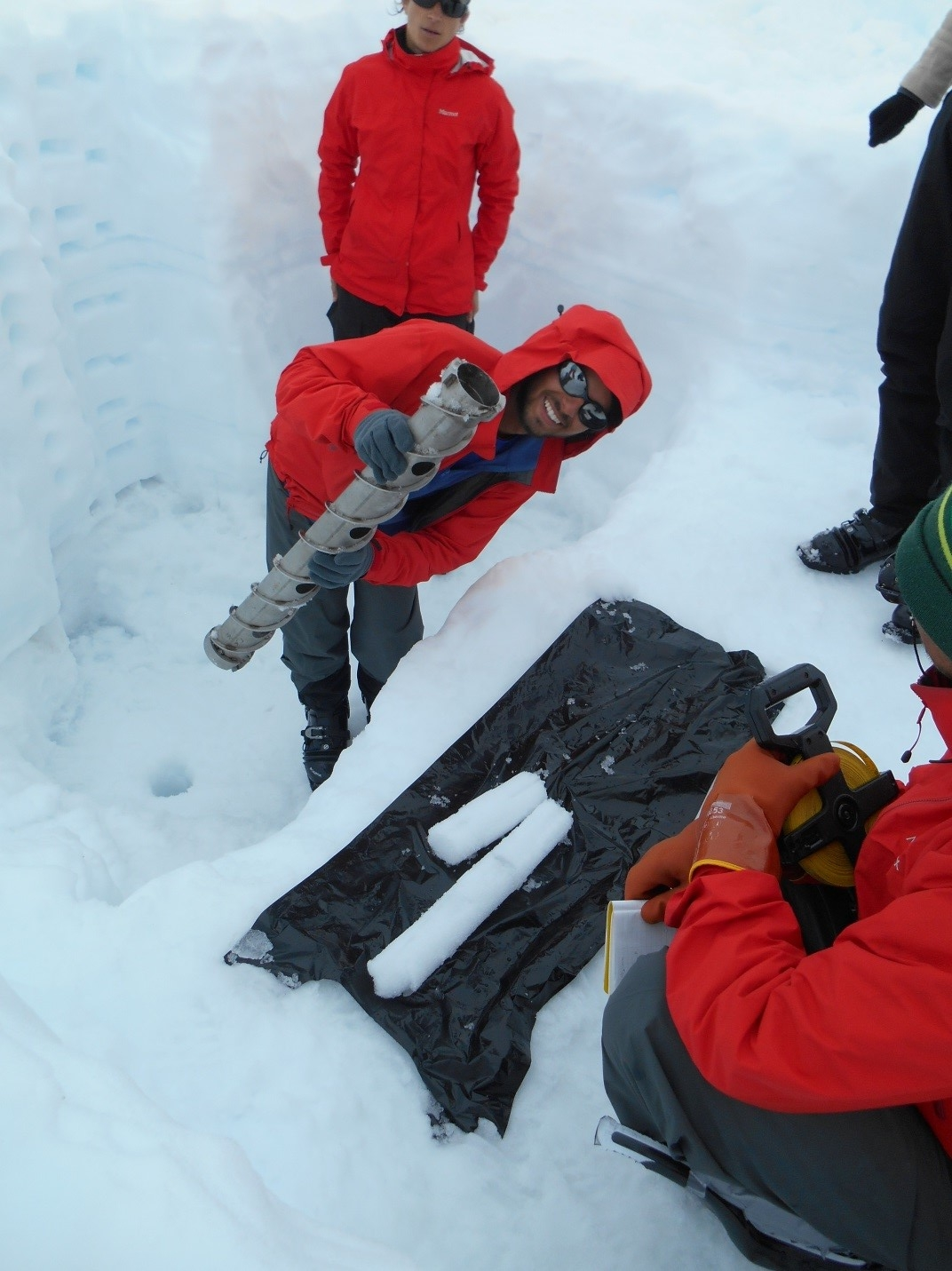 Austin C. with ice core samples from snow pit on the Taku Glacier. (photo credit Jutta Hopkins-LeCheminant)