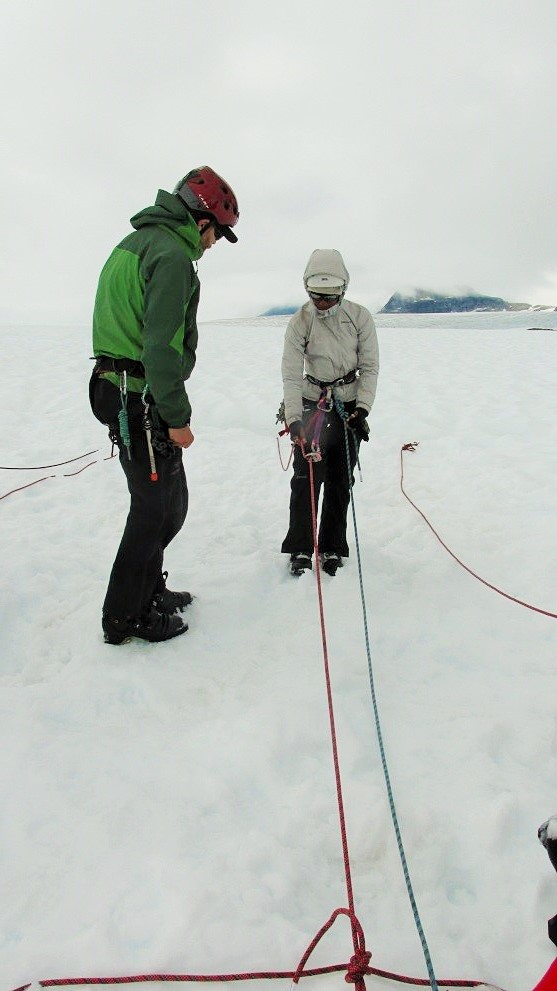 Ari tying her final safety knots with the crevasse opening several meters behind her. Photo by author.