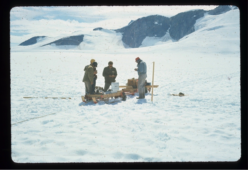 Dr. Tom Poulter (right) checking the seismic record on the Taku plateau; Barry Prather in sunglasses is also reading the printout; Poulter seismic shooting pole next to him