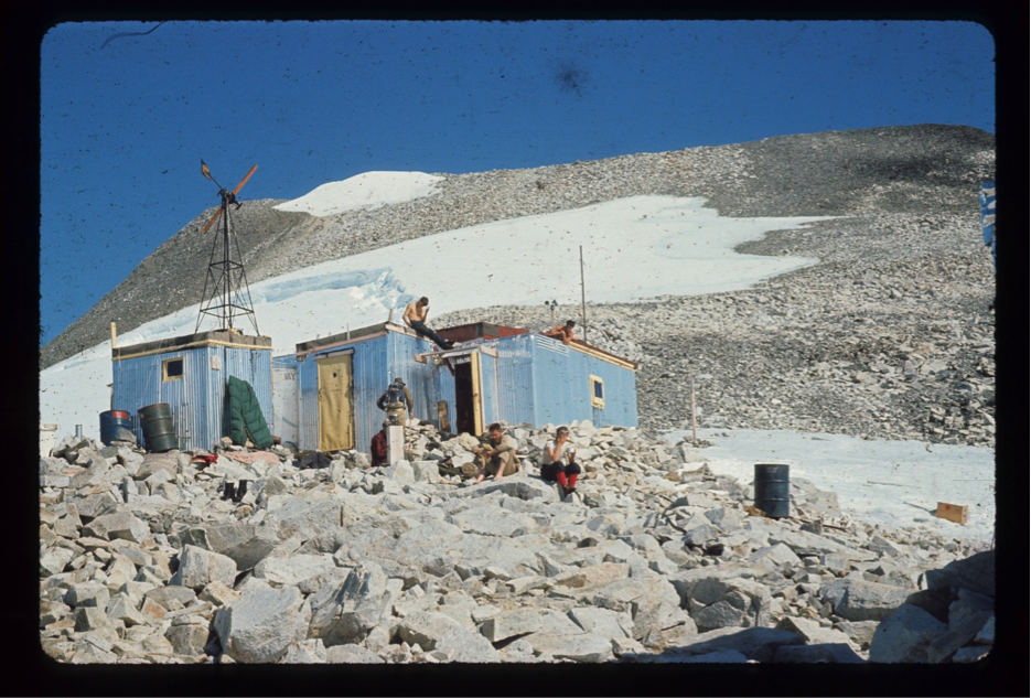 "Camp 8 July 25, 1965; the team lounging include Scott Hulse and Bill Patzert (sunbathing on the roof), Bill Isherwood (back to camera with pack), Chris Egan (red shirt seated behind solarimeter) Ty Kittridge (seated on rock with his Bull Mastiff ""Siggy"") and Dennis Cowels (red socks)"