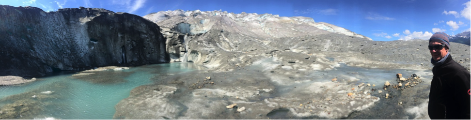 The glacier's complex hydrology system displays a waterfall emerging near the terminus.