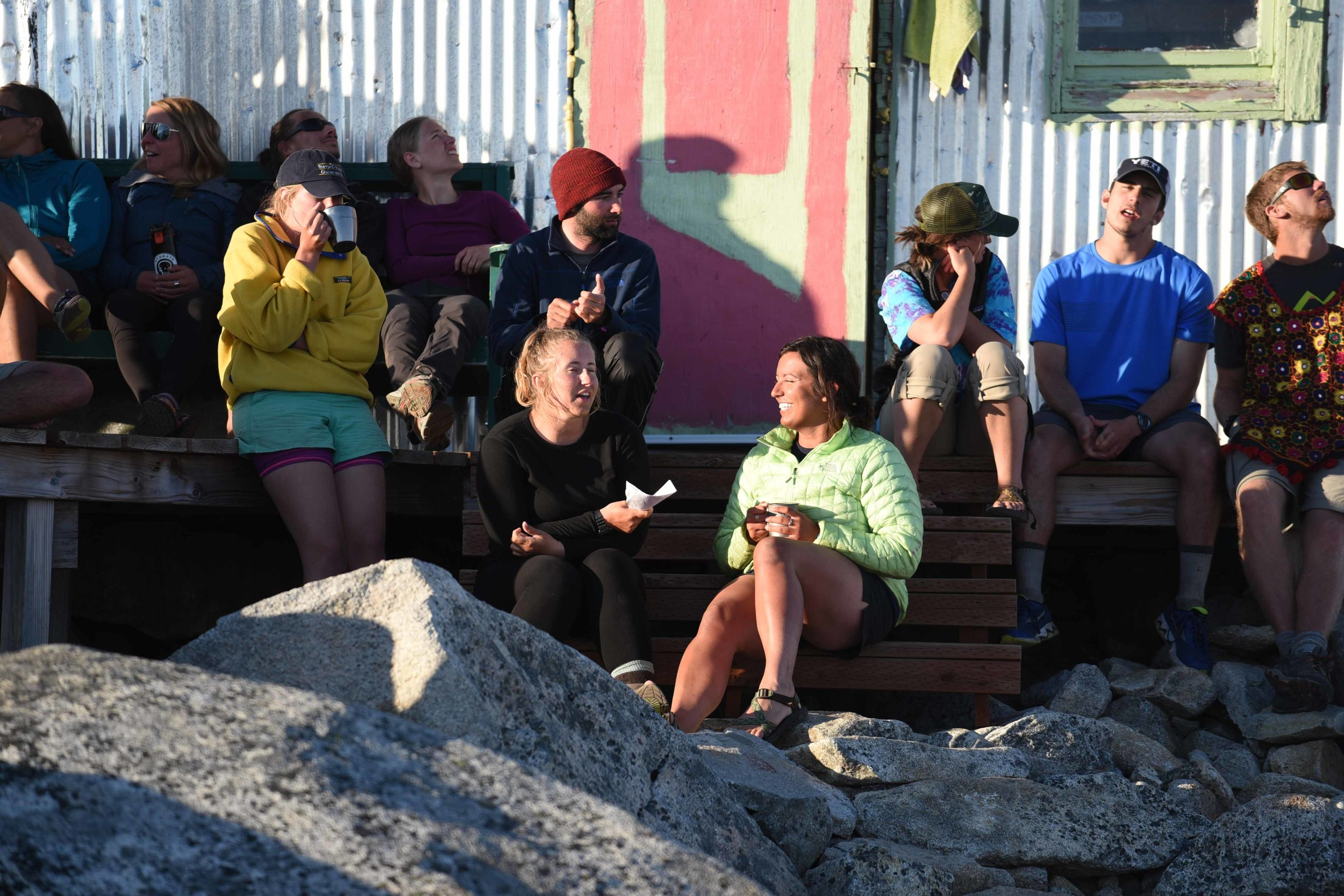 The author, in yellow with cup in hand, sharing stories in camp with fellow JIRPers. Photo courtesy of PBJ Photography.