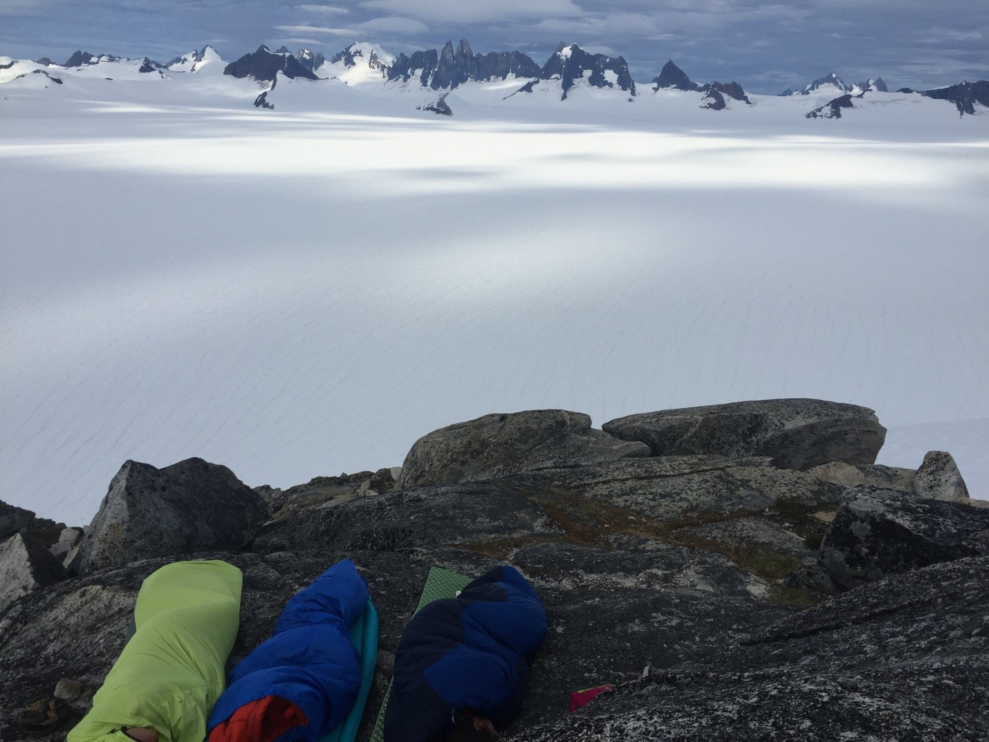 My first night in Camp 10, sleeping in the best bivy spot. The view is looking across the Taku Glacier at the Taku Towers (they can be spotted right in the middle of the peaks shown). This night included both an early morning sprinkle and a glaring sun wake-up. Photo by Auri Clark.