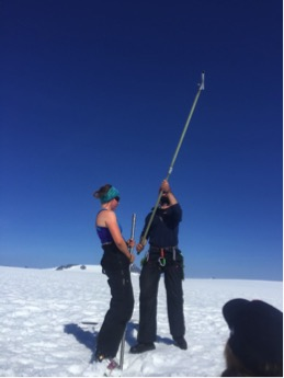 Caption: Kit Cunningham and Chris Miele adding flights to the drill (partly lowered in the hole). Photo credit: Sarah Fortner