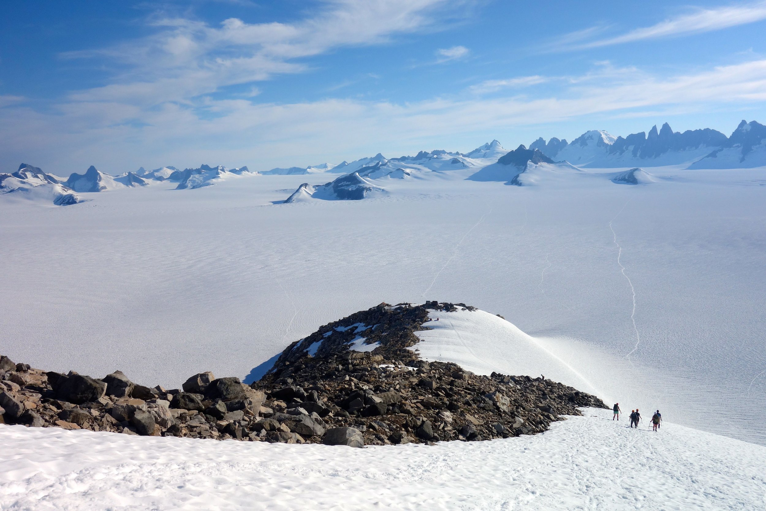 The hike down to camp for dinner. At the top of the rocky hilltop in the fore ground you can pick out the buildings of our largest camp. Beyond camp, Taku Glacier flows from right to left in front of the distant Taku Towers. Photo credit: Kenzie McAdams.