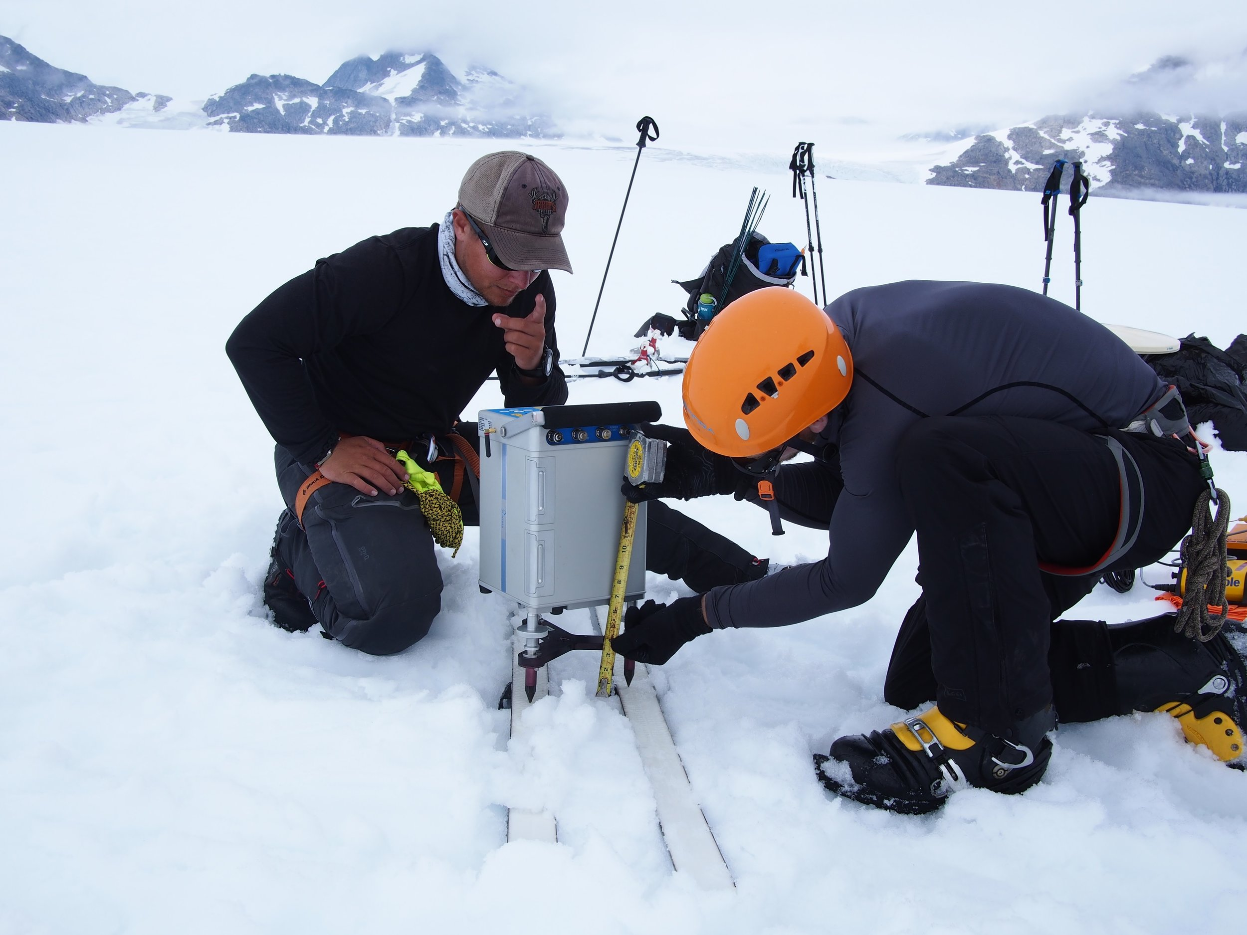 Students DJ Jarrin and Riley Wall set up the delicate gravimeter. The gravimeter measures tiny anomalies in the local gravity, which the students use to deduce information about the bedrock buried beneath almost a mile (1500 m) of ice. Photo credit: DJ Jarrin.