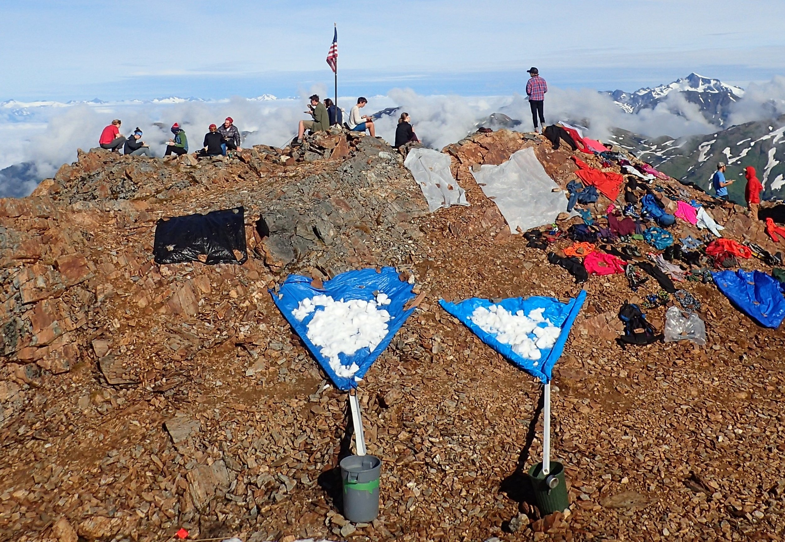 The water supply at Camp 17 is shown above, displaying the tarps onto which we shovel snow from the patch just off the bottom of the photo. A piece of white gutter connects the tarp to the trash barrel, into which the melted water drains. A sauce pan can be seen on the side of the barrel on the right, used to scoop water into buckets for transport. Photo credit: Ann Hill.