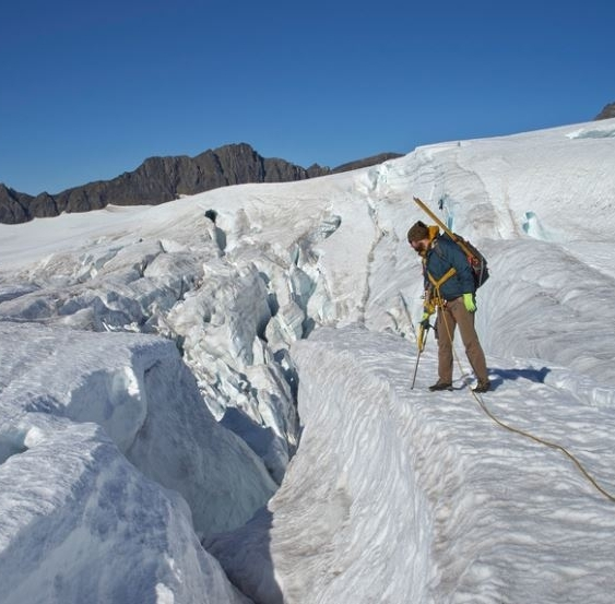 Chris looks down into a crevasse on the Wolverine Glacier.