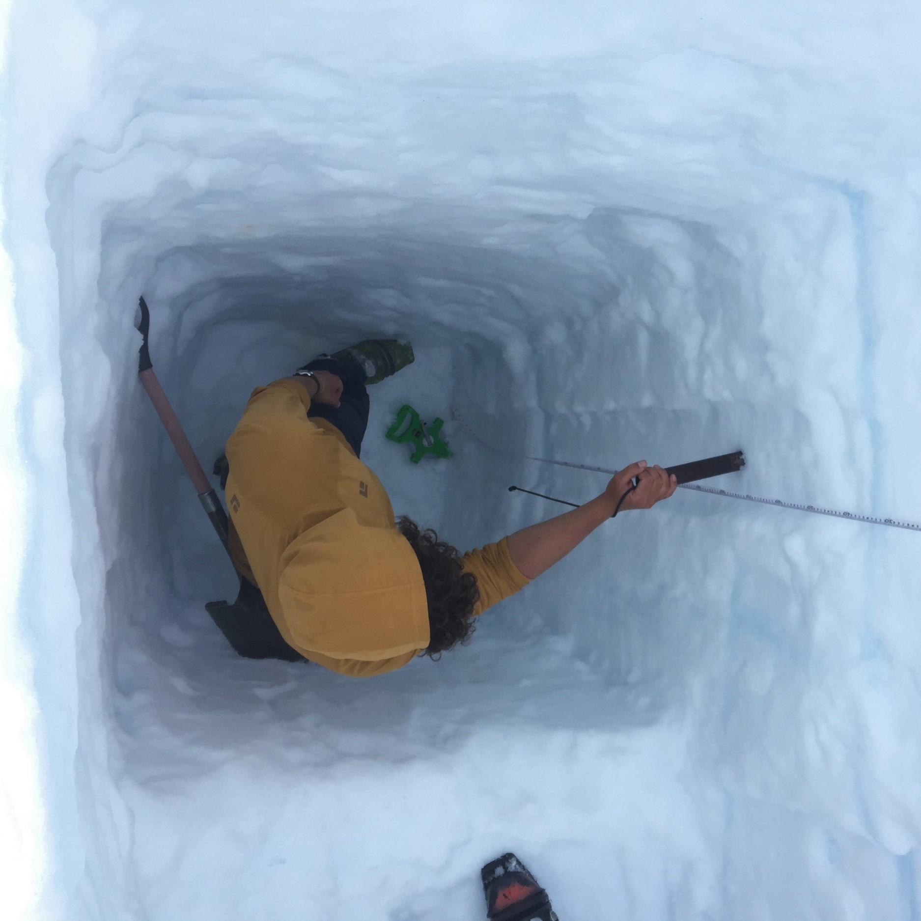 Avery Stewart, a student researcher with the Mass Balance team, collects a snow density sample in a pit. Photo credit: Susannah Cooley.