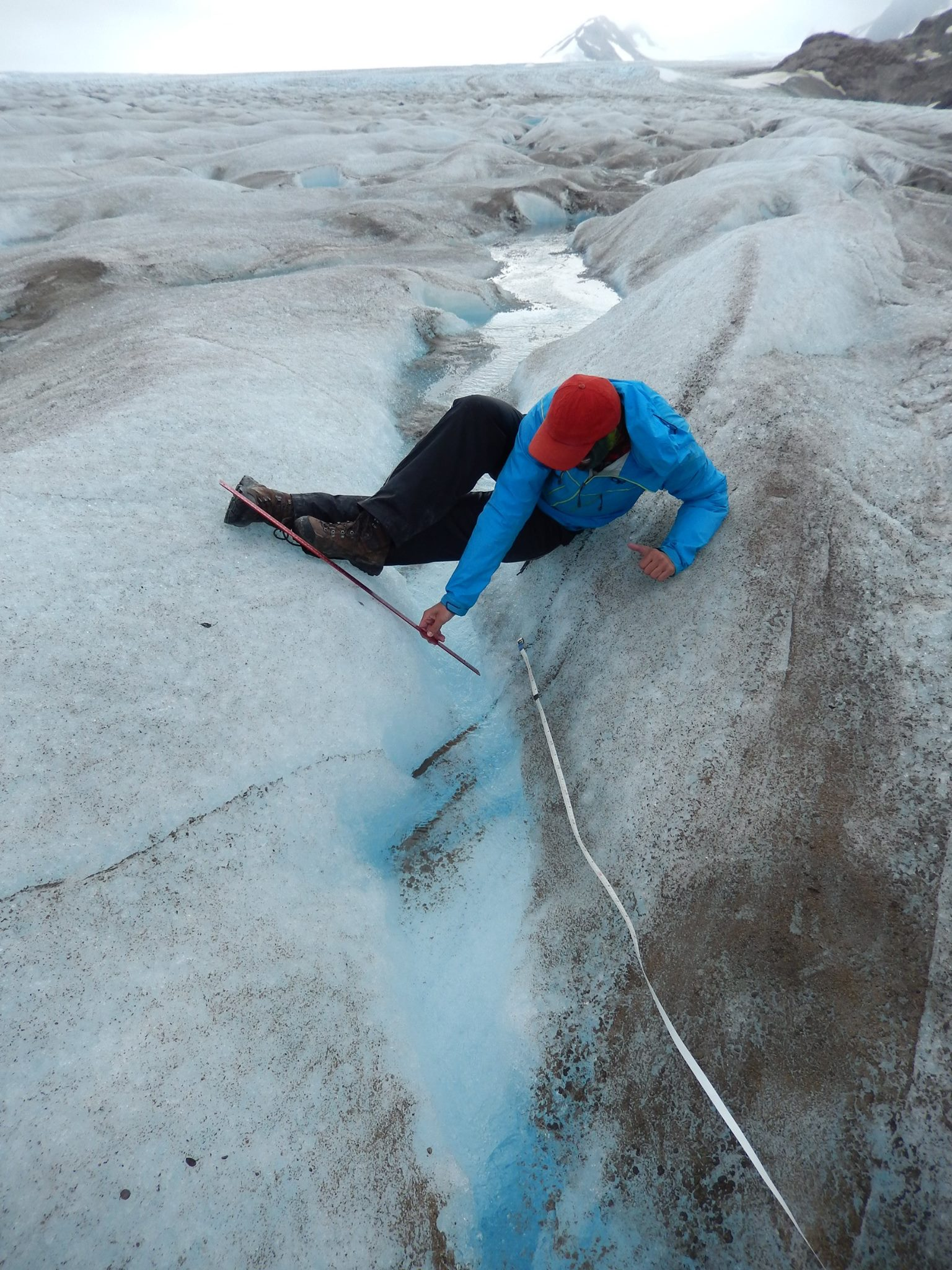 A biogeochemistry student researcher measures the dimensions of a supraglacial stream in the ablation zone of the Llewellyn Glacier. Photo credit: Molly Peek.