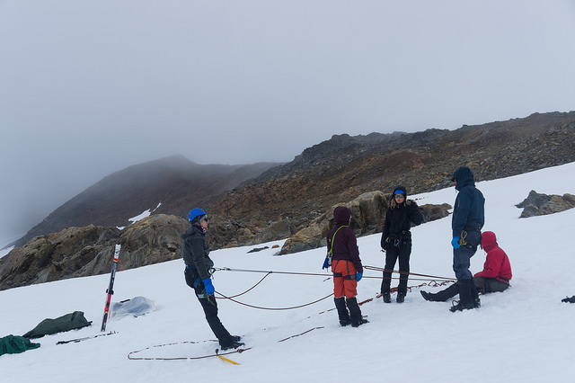 Staffer Annika Ord (orange pants) works with students and a new faculty member on a crevasse rescue system with a four-person rope team. Everyone to work through new skills on flat or gently sloping ground before jumping onto a steep snow slope. Photo: Daniel Otto.