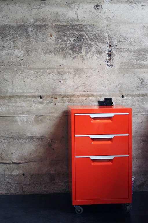 Red file cabinet against exposed wall