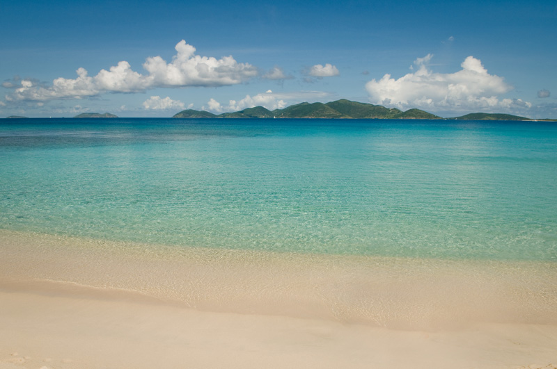 Smuggler's Cove's white sand beach with it's coral reef on the left and Jost Van Dyke in the background