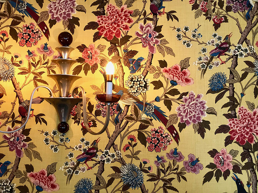Bold, floral wallpaper adorns the Dining Room at Ockenden Manor, Cuckfield