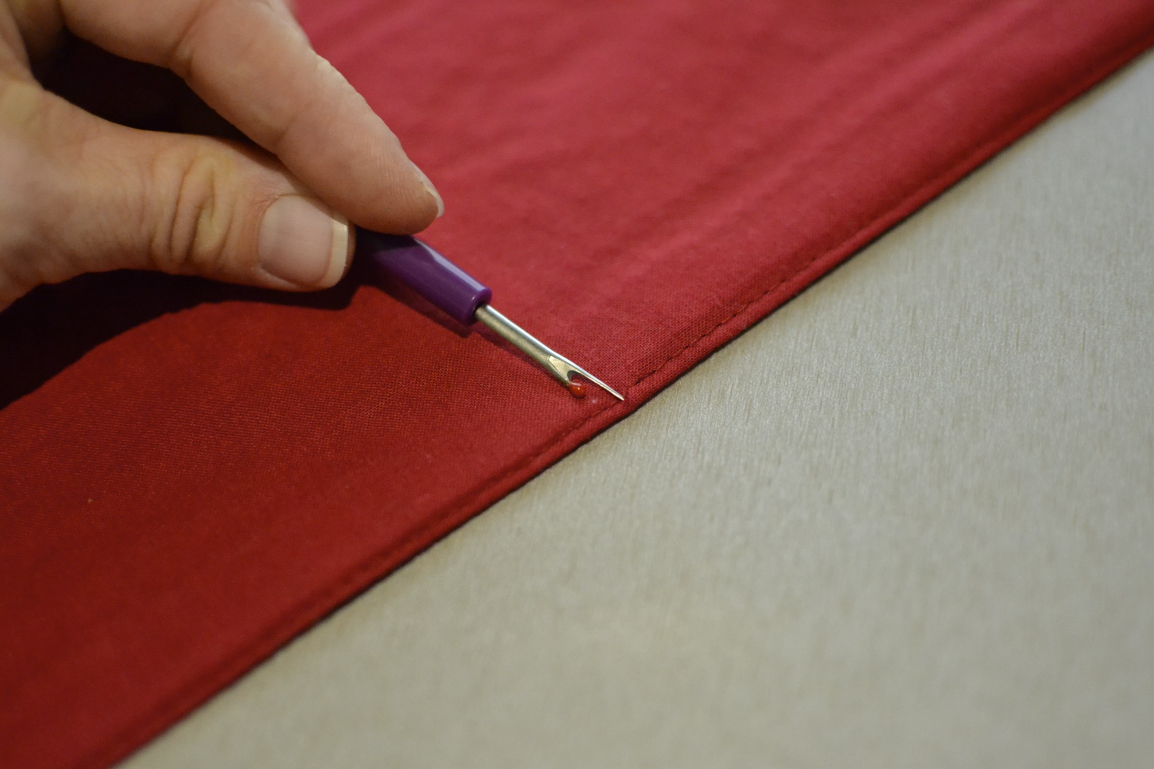"""begin in the middle, on the back side of the placemat, by gently pulling at the thread with your seem ripper. cut through the thread and carefully unthread the existing stitching about 3"""" to each side of where you started. it helps to have about a 6"""" opening to add the stuffing. be careful not to break the thread...you need for it to be long enough to tie off once you have opened up the seem."""