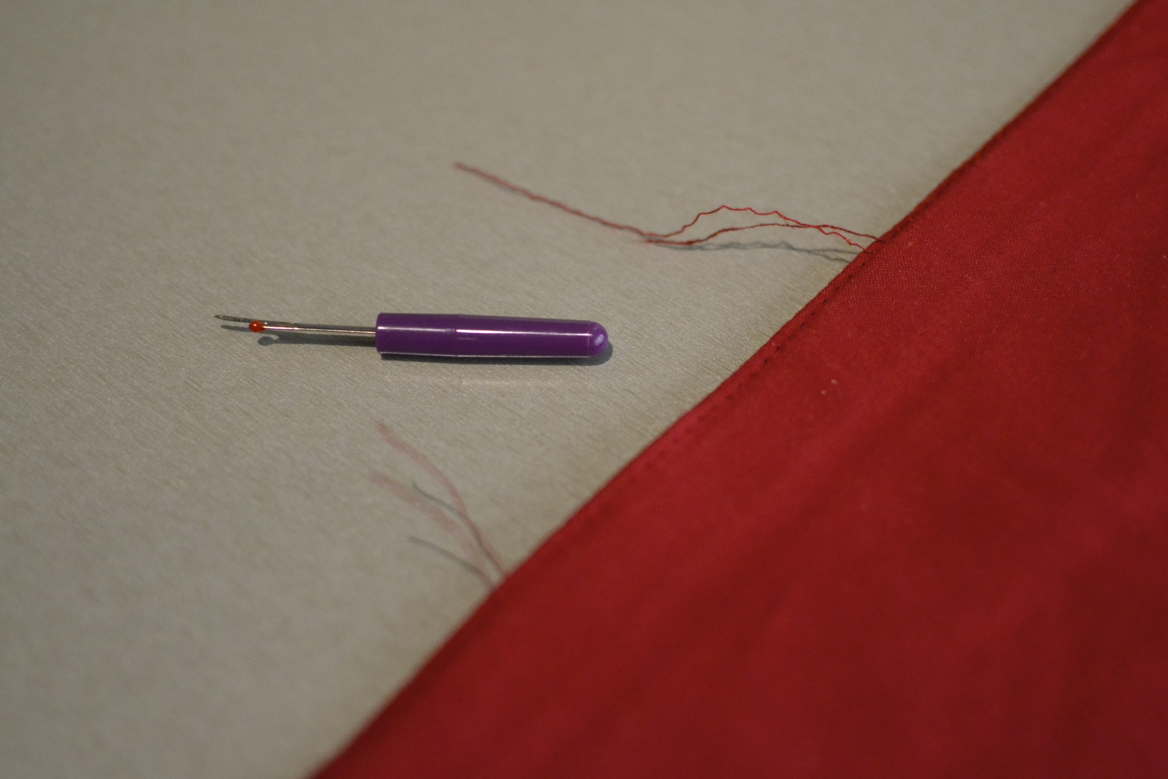 """once you have created an opening about 6"""" wide, pull both lengths of thread through to the back and double tie them off before trimming. this will prevent the seem from opening any further."""
