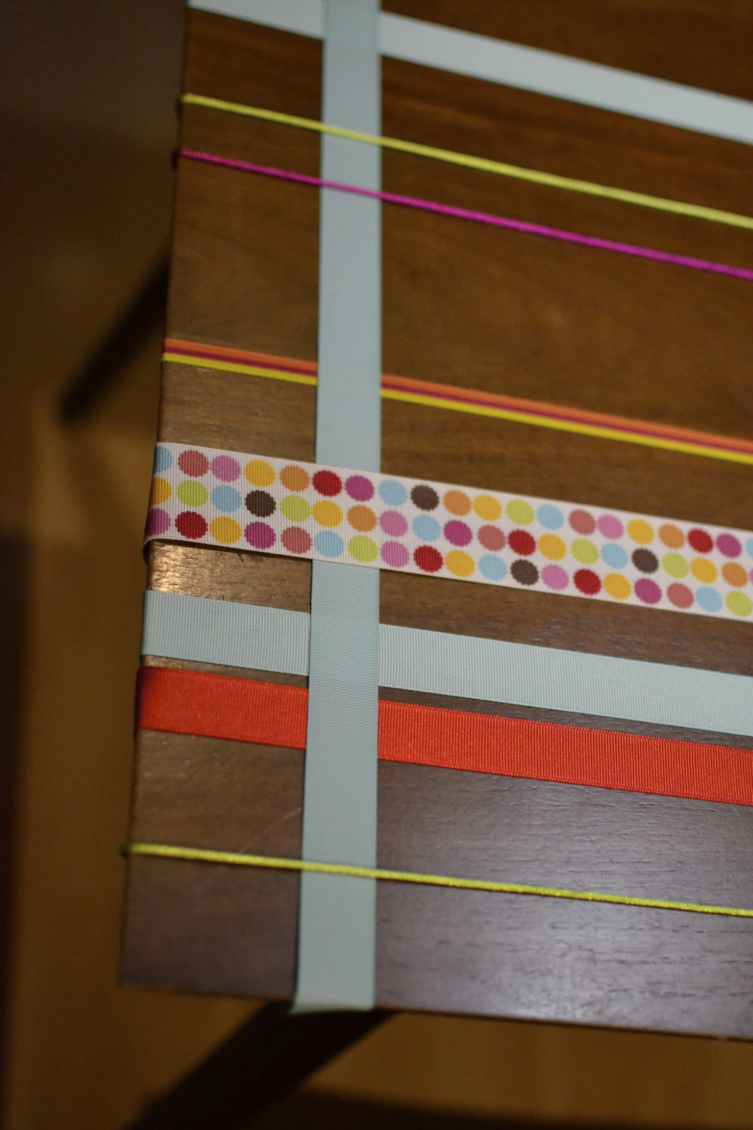 for the width of the table, tape one end of the ribbon underneath your table and begin to weave it over and under the ribbons stretching lengthwise. and again, tape ribbon end in place.