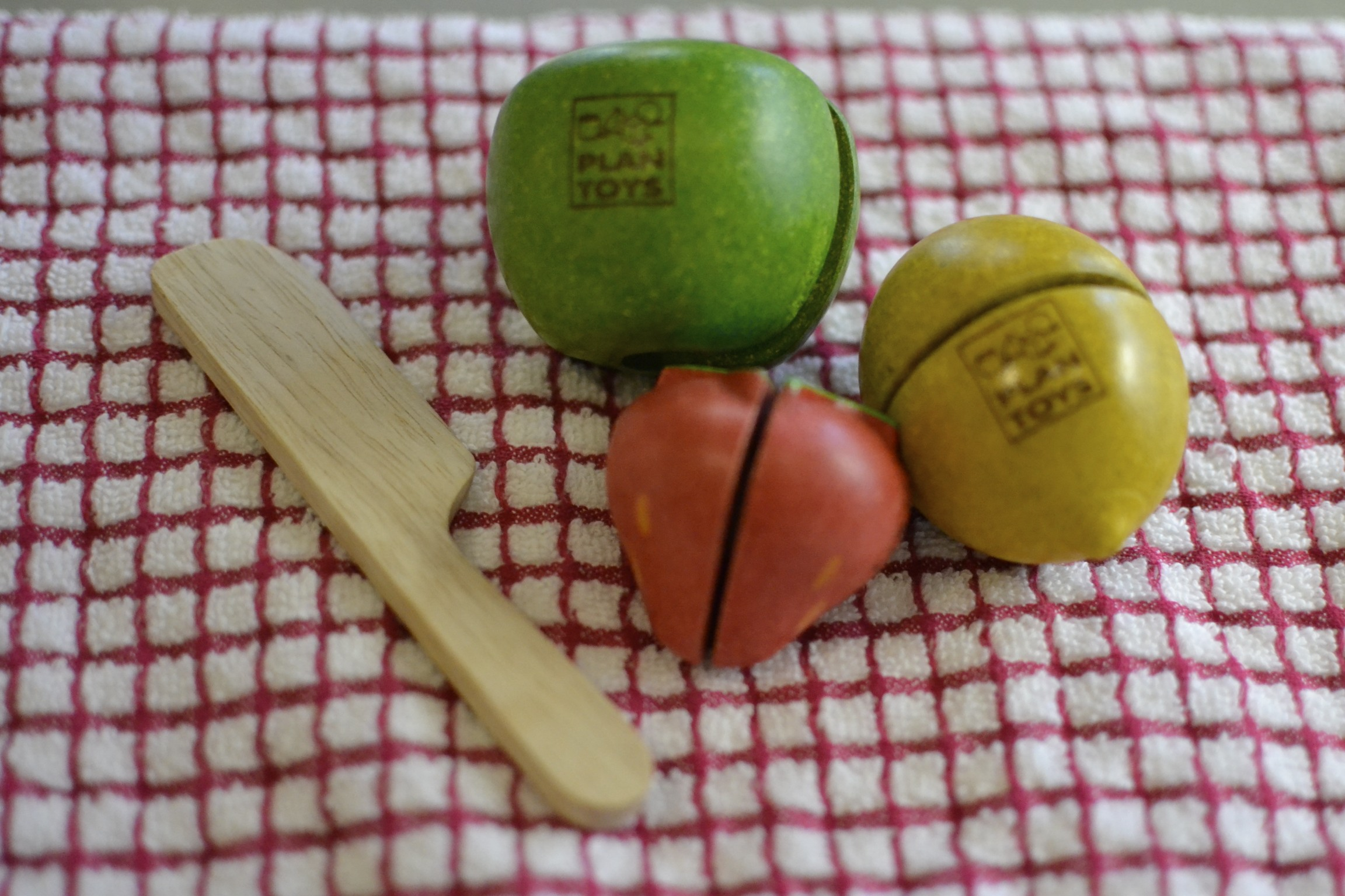 """enjoying our new plan toys fruits. c has been """"cutting"""" and """"chopping"""" them like crazy! the two halves are attached to each other with velcro and the wooden knife cuts through them and pulls them apart. so clever."""