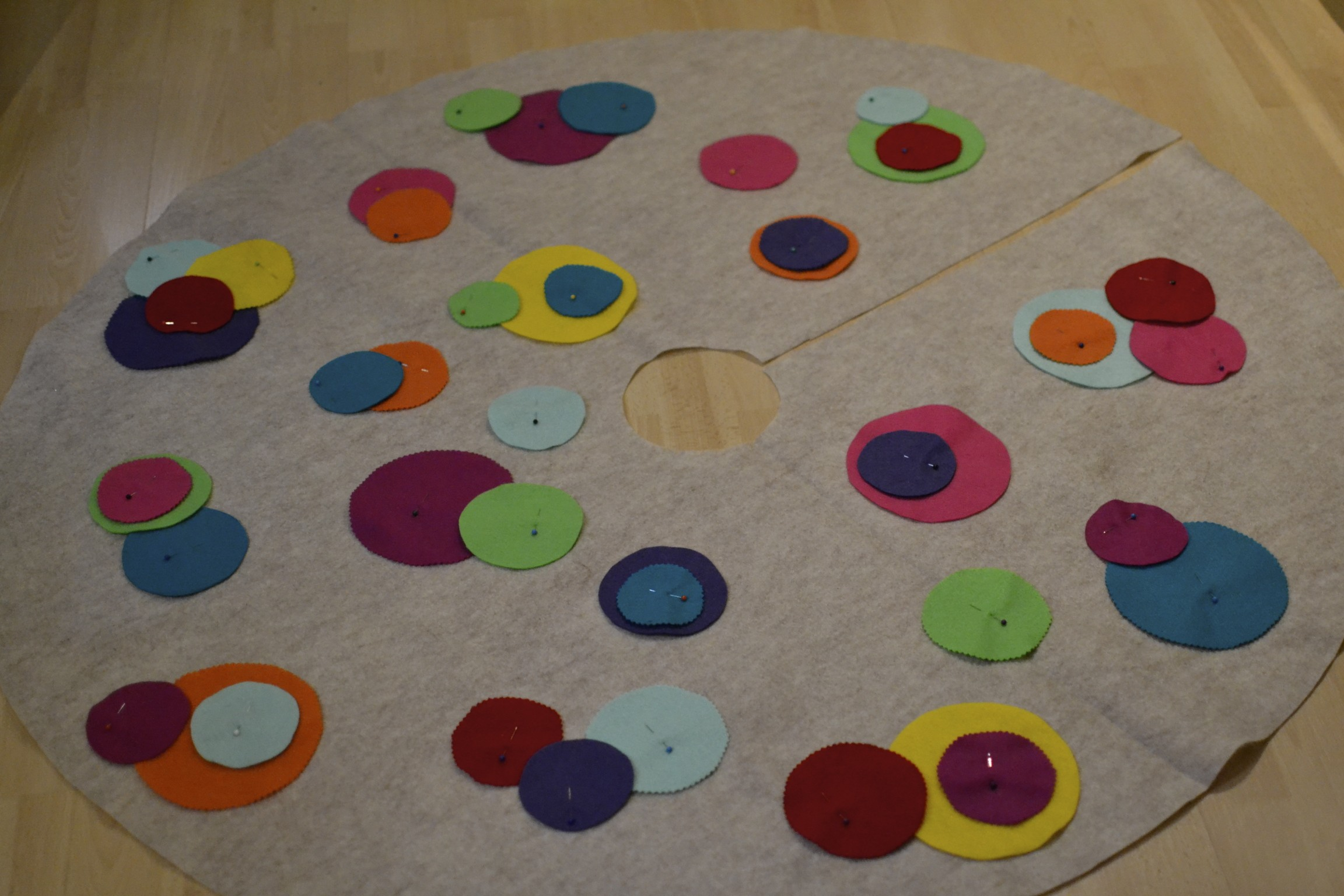 """i used an oatmeal felt for the base and actually just used my old tree skirt to trace the circle. this is a 48"""" diameter circle so, purchasing 1 1/4 yards of felt would do the trick. (this skirt turned out to be pretty large. you could definitely do with using 1 yard of fabric and making the skirt 36"""" in diameter.) then i used 3 sizes of cups to trace circles on sheets of various felt colors. i cut some of the circles out with regular scissors and others with pinking shears to provide different textures."""